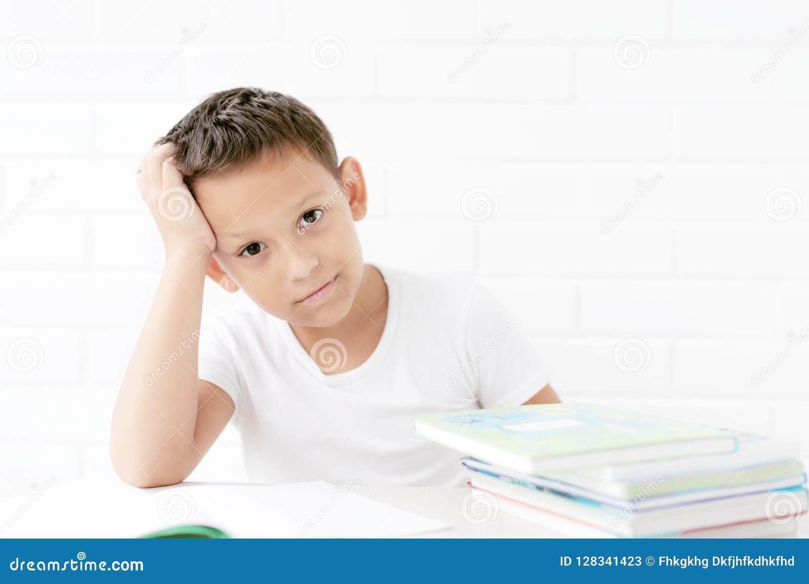 Uczeń siedzi przy stołem i uczy się lekcje