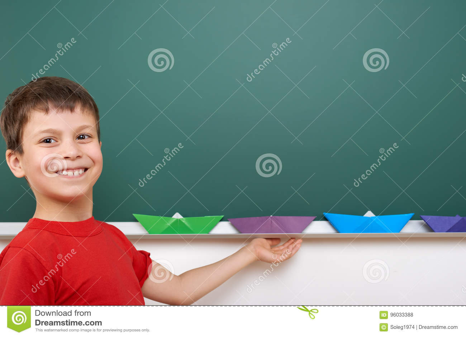 Uczeń z papierową łódkowatą sztuką blisko blackboard, opróżnia przestrzeń, edukaci pojęcie