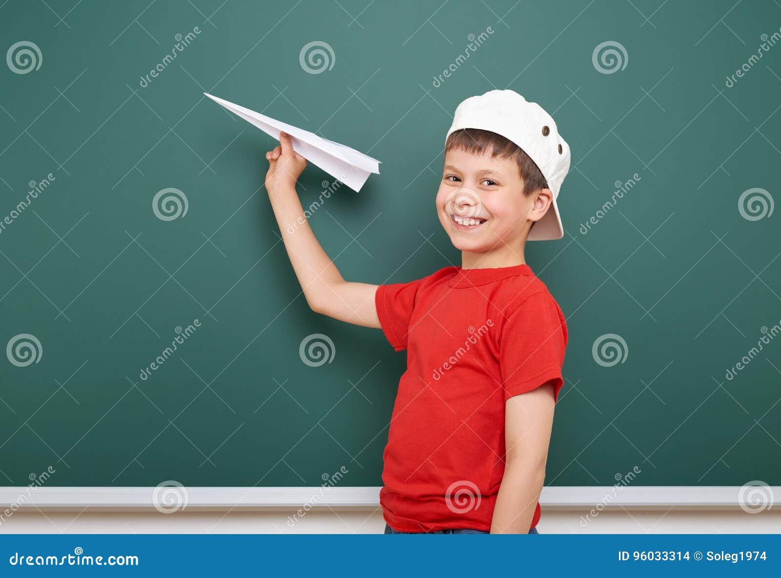 Uczeń z papieru samolotu sztuką blisko blackboard, opróżnia przestrzeń, edukaci pojęcie