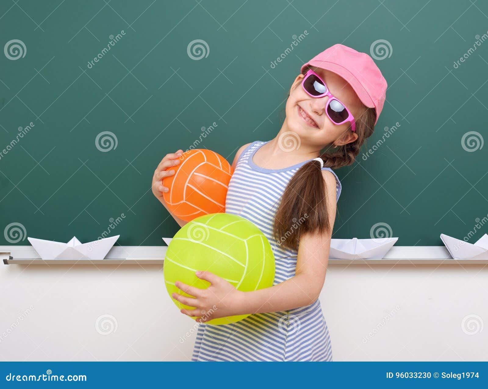 Uczennica z papierową łodzią i balon bawić się blisko blackboard, pusta przestrzeń, edukaci pojęcie