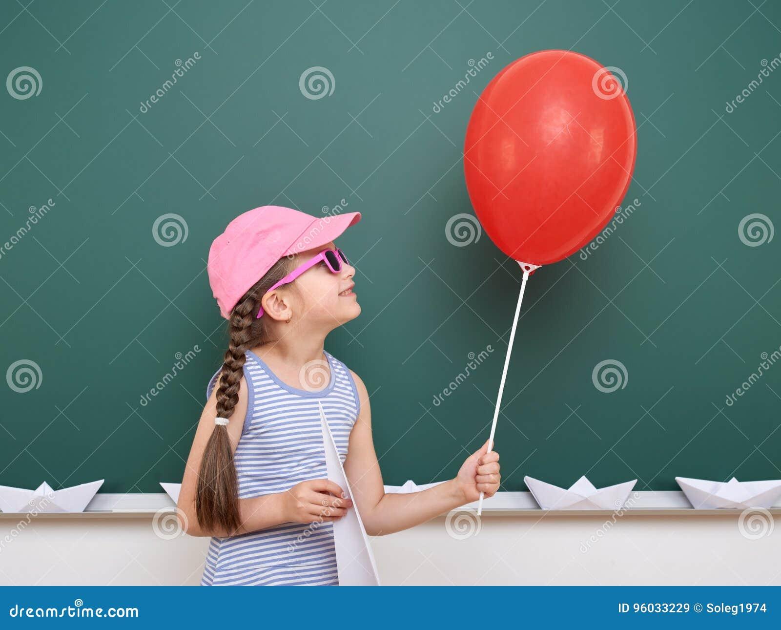 Uczennica z papieru samolotem i balon bawić się blisko blackboard, pusta przestrzeń, edukaci pojęcie
