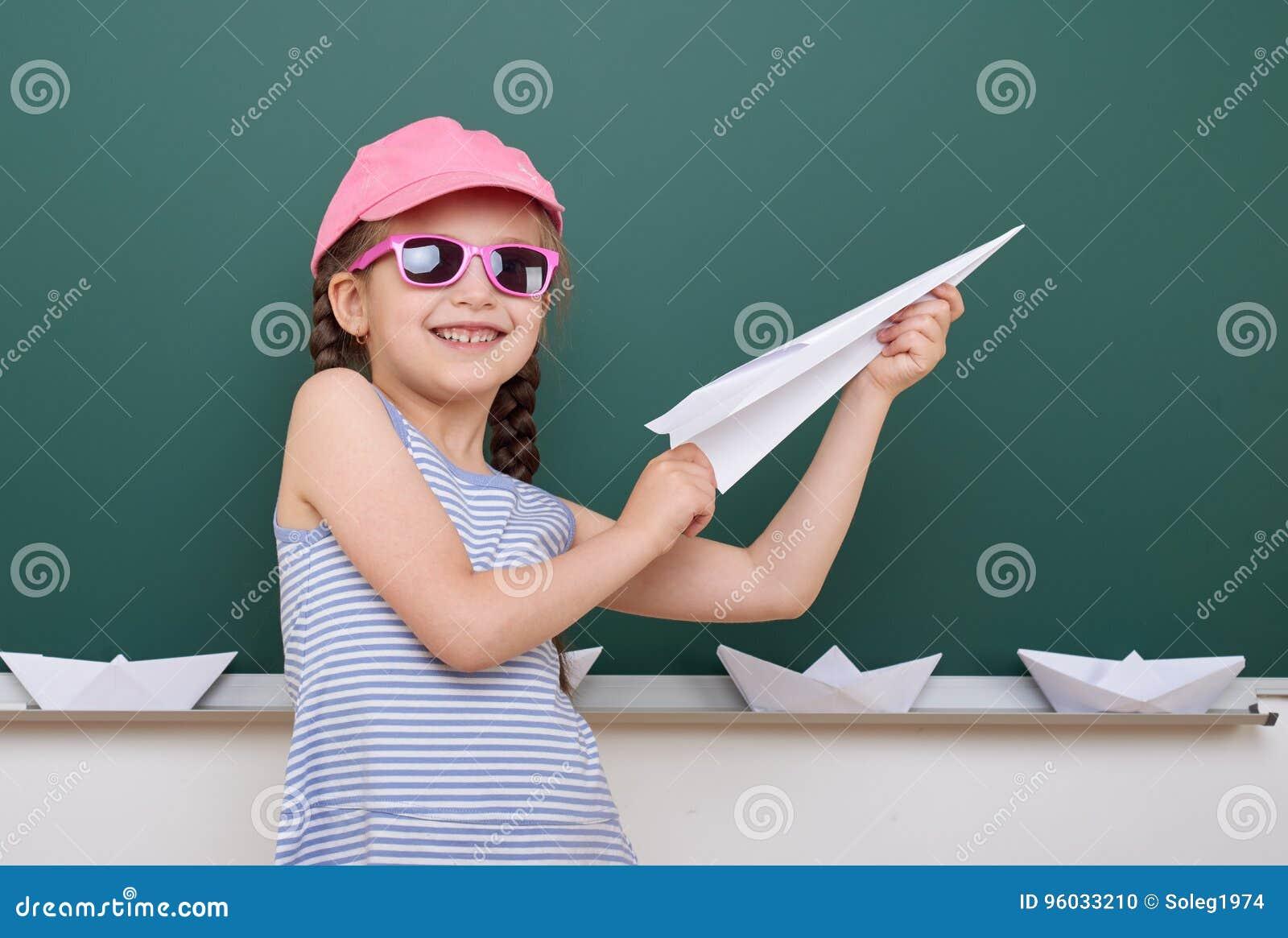 Uczennica z papieru samolotu sztuką blisko blackboard, opróżnia przestrzeń, edukaci pojęcie
