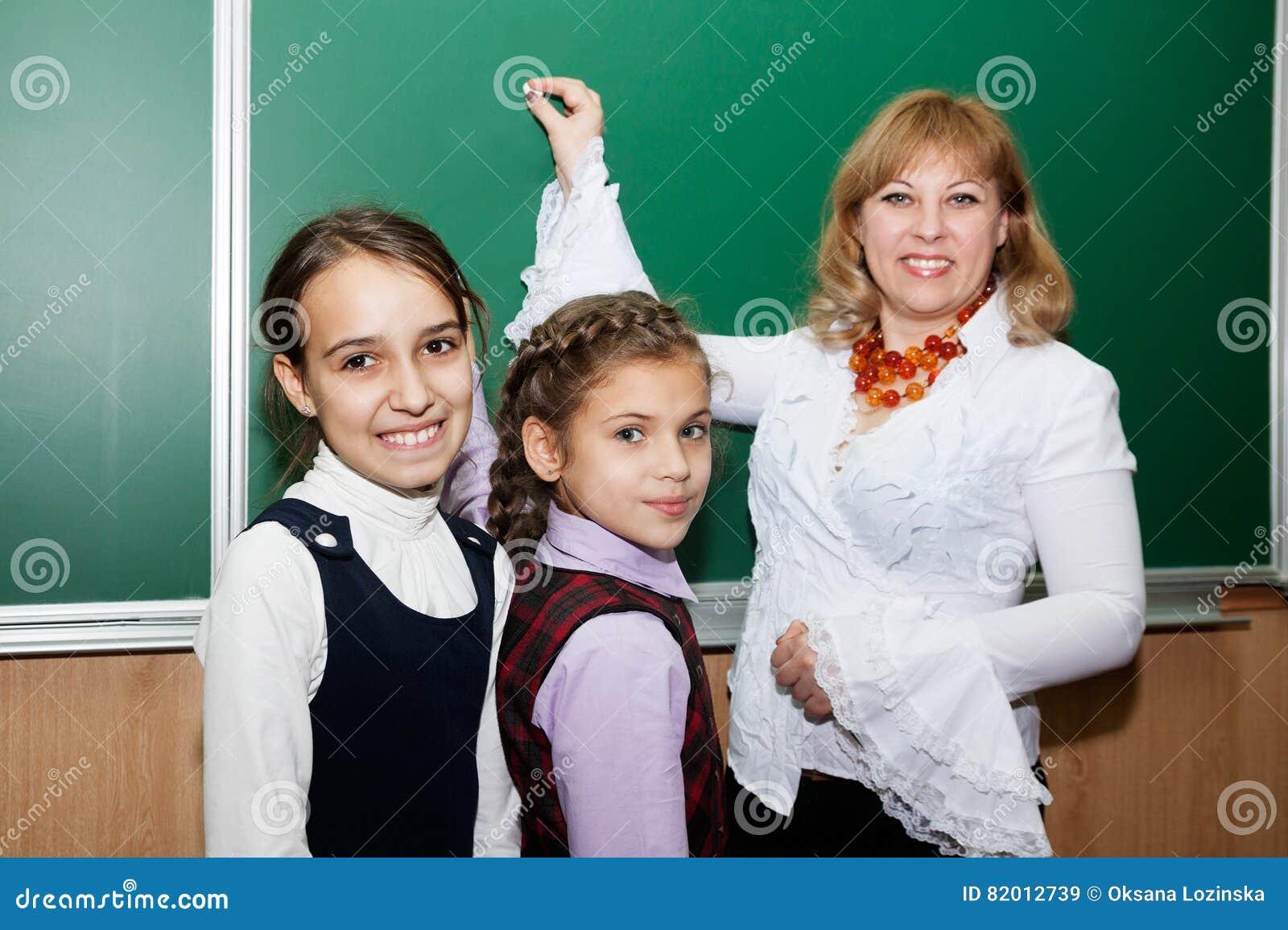 Uczennicy i nauczyciel przy blackboard