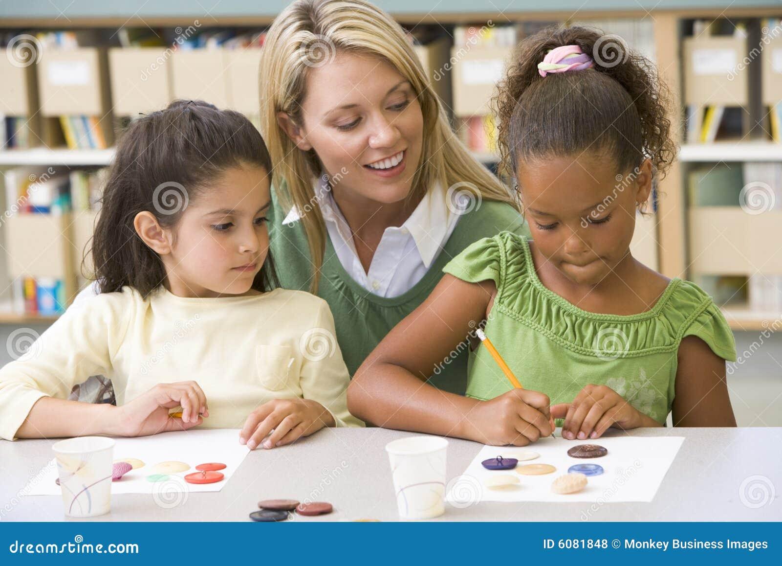Uczniów sztuki klasy siedzący nauczyciel