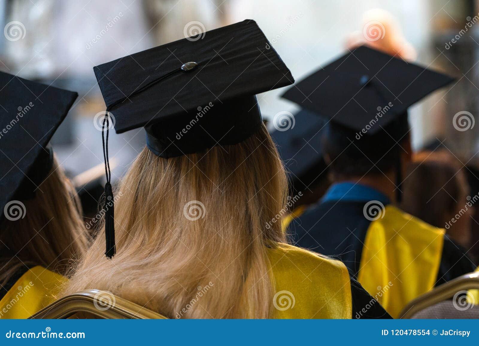 Ucznie jest ubranym togi i kapelusze siedzi indoors, czekający rece
