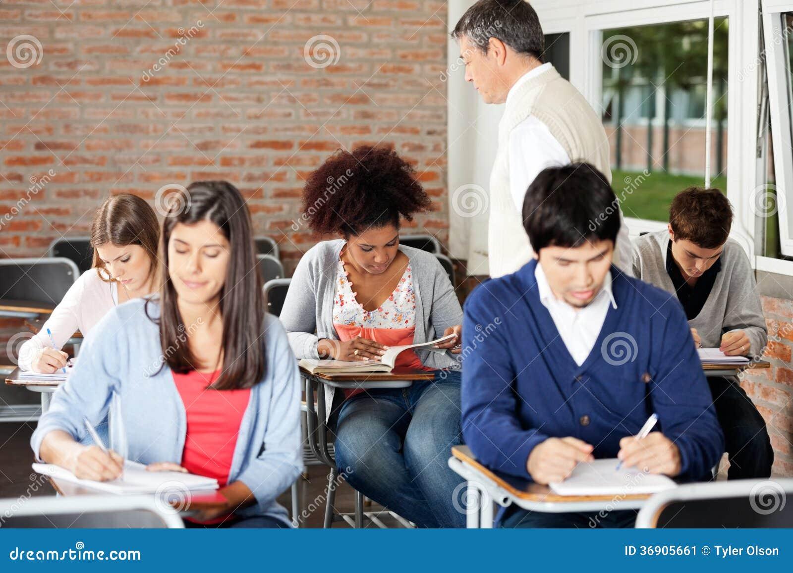 Ucznie Pisze egzaminie Podczas gdy nauczyciela Doglądać