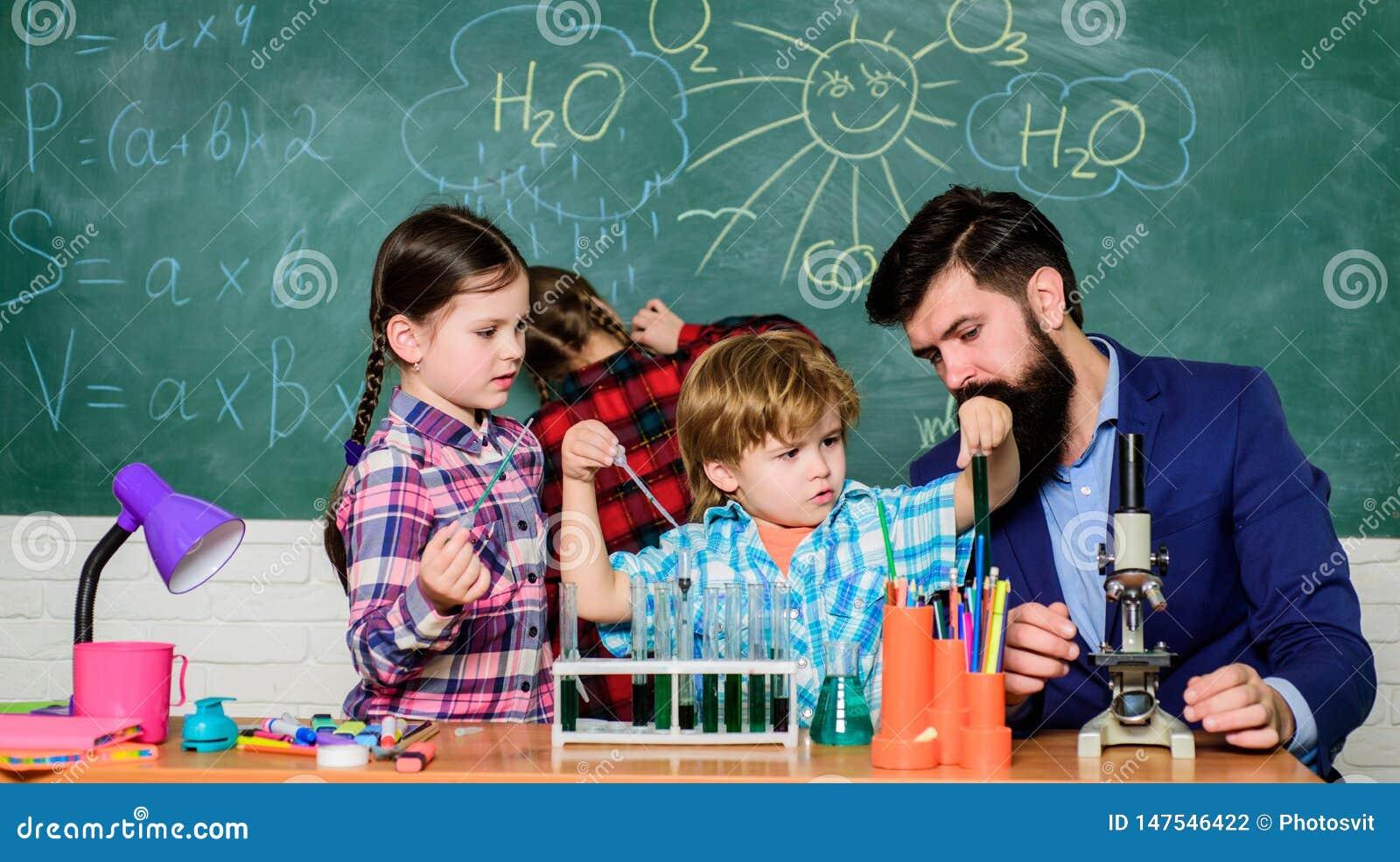 Ucznie robi nauce eksperymentuj? z mikroskopem w lab szko?a ?artuje naukowa studiowania nauk? Szcz??liwi dzieci