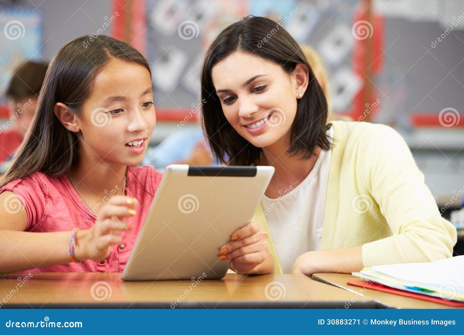 Ucznie W Klasowej Używa Cyfrowej pastylce Z nauczycielem