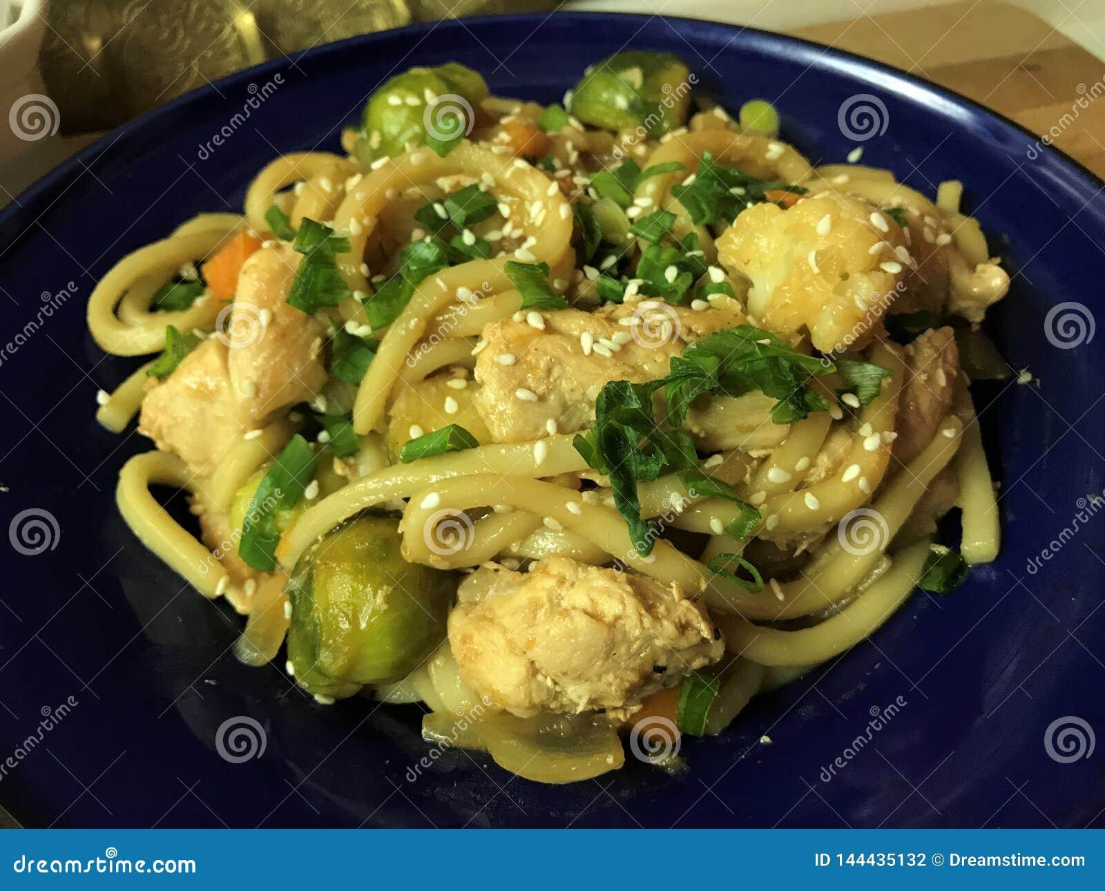 Udon avec le poulet et le sauté de légumes en sauce à teriyaki