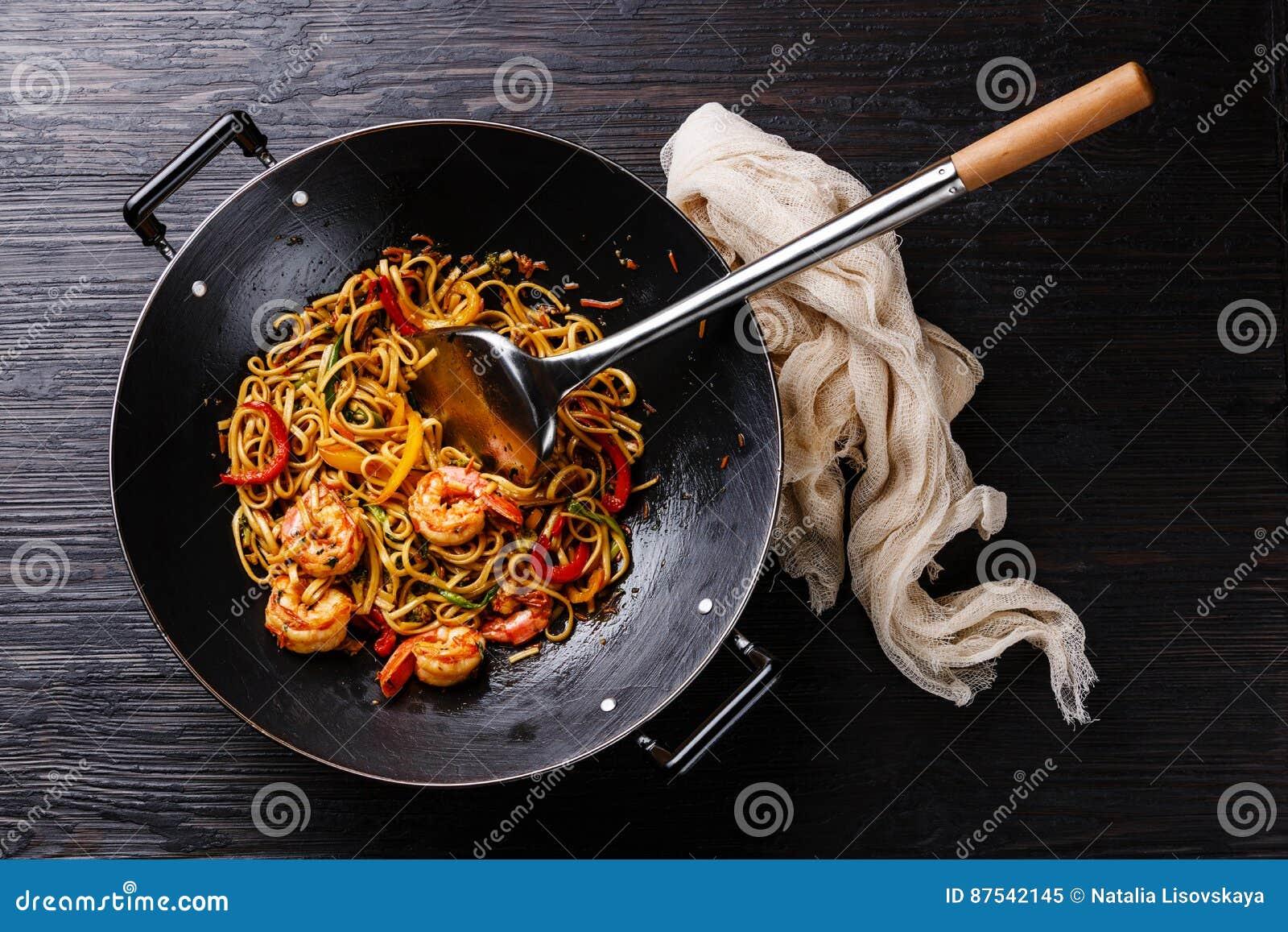 Udon stir fry noodles with prawn shrimp and vegetables in wok