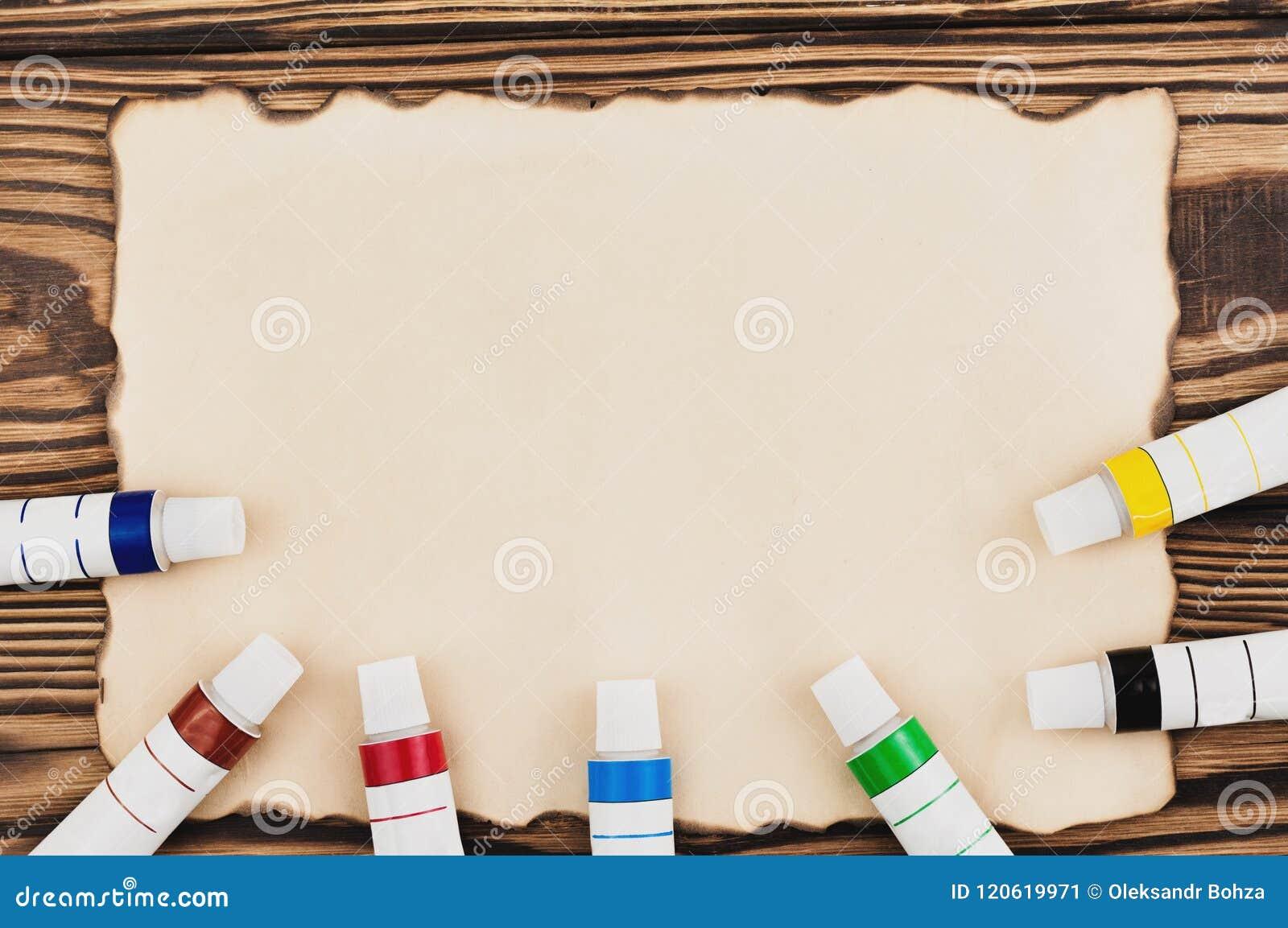 Udział kolorowe akrylowe farby w zamkniętych tubkach na burnt prostokąta pustym papierze