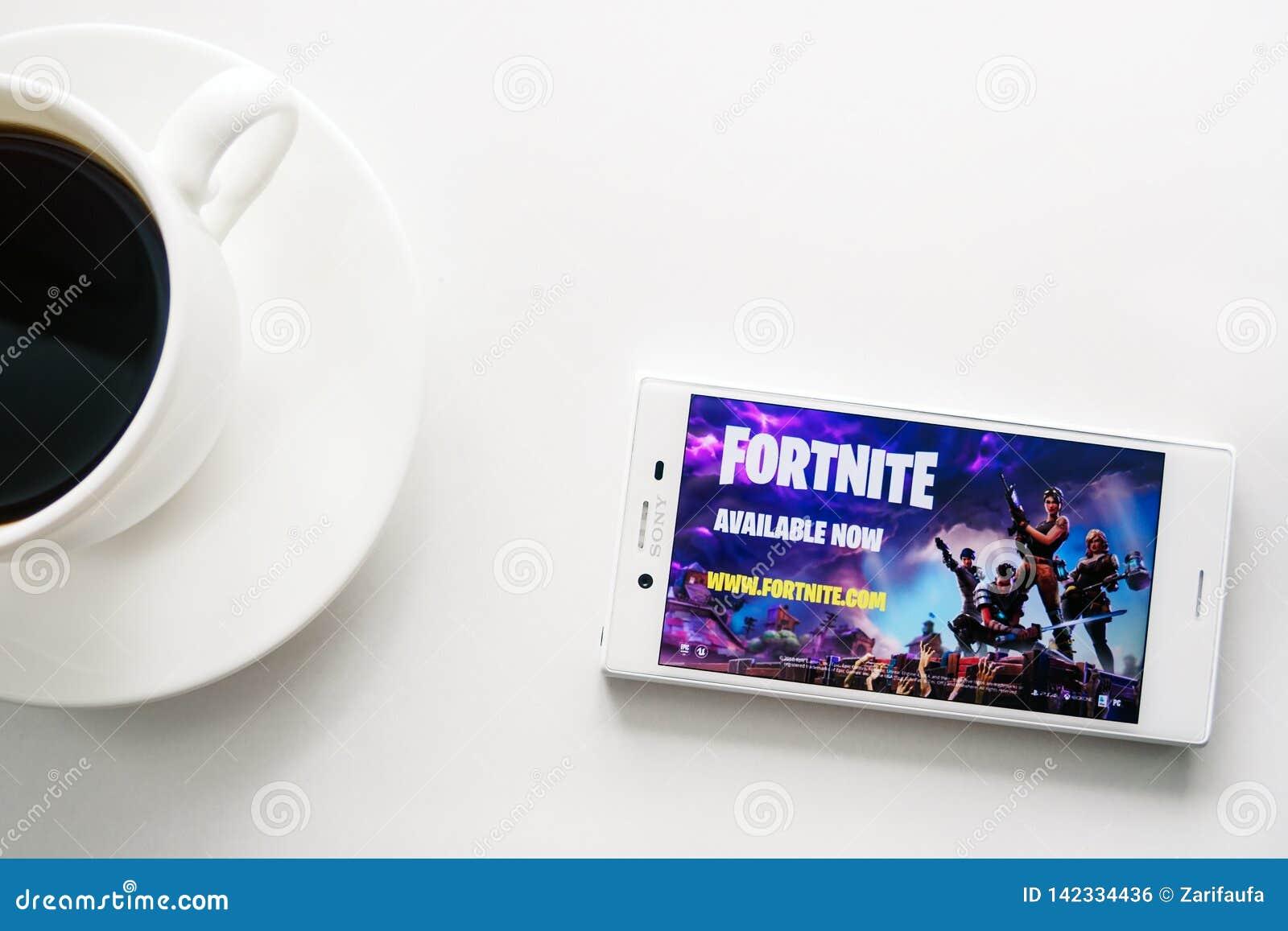 Ufa Ryssland - mars 15, 2019: Fortnite lek på den Android smartphoneskärmen, telefonen och kaffekoppen på vit bakgrund, kopiering
