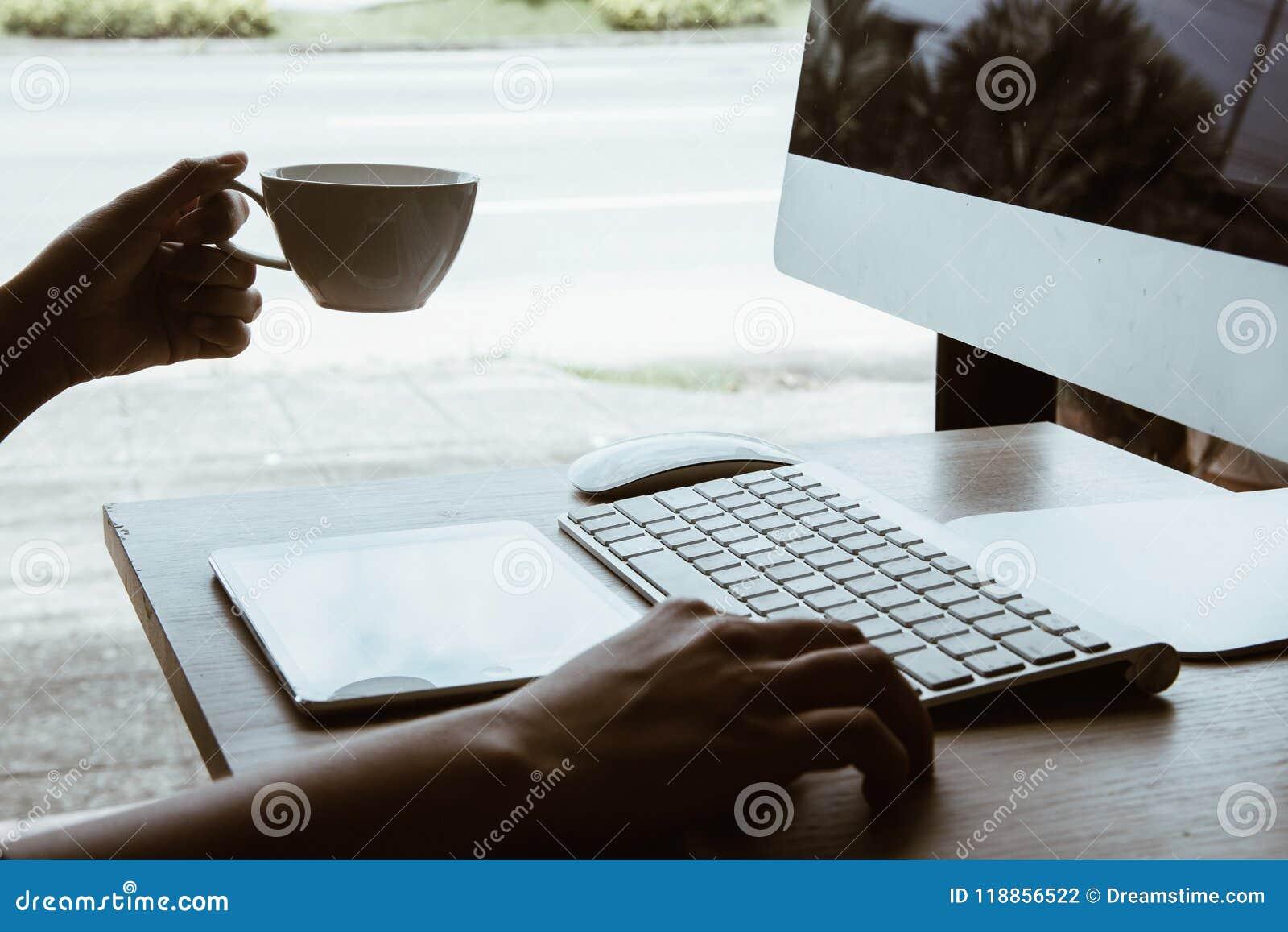 Ufficio che lavora alla tavola dell ufficio con il posto di lavoro della tavola dell ufficio di affari della tazza del computer e