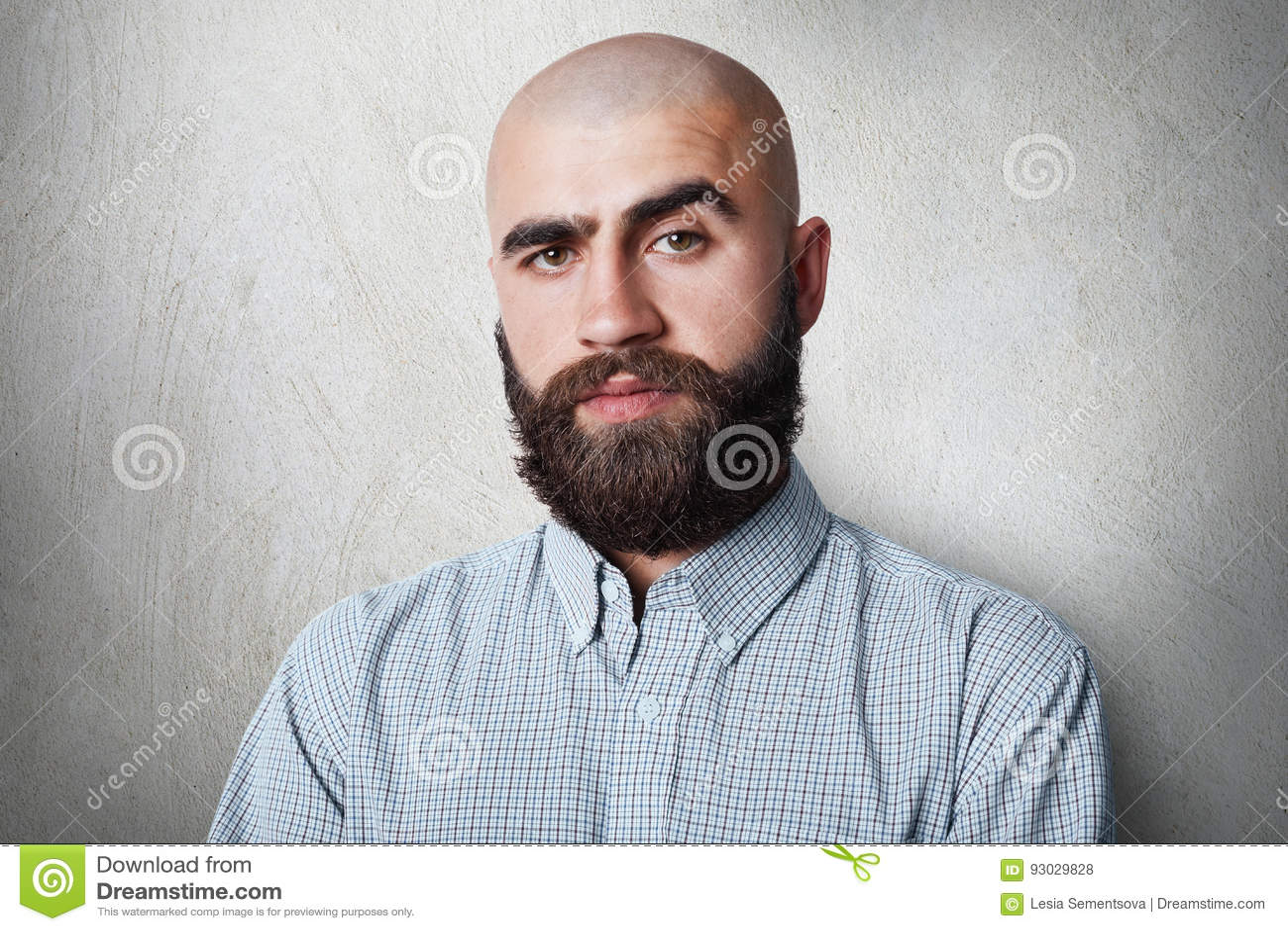 Ufna łysa samiec jest ubranym sprawdzać koszula ma ponurego wyrażenie pozuje przeciw bielu plecy z gęstymi czarnymi brwiami i bro