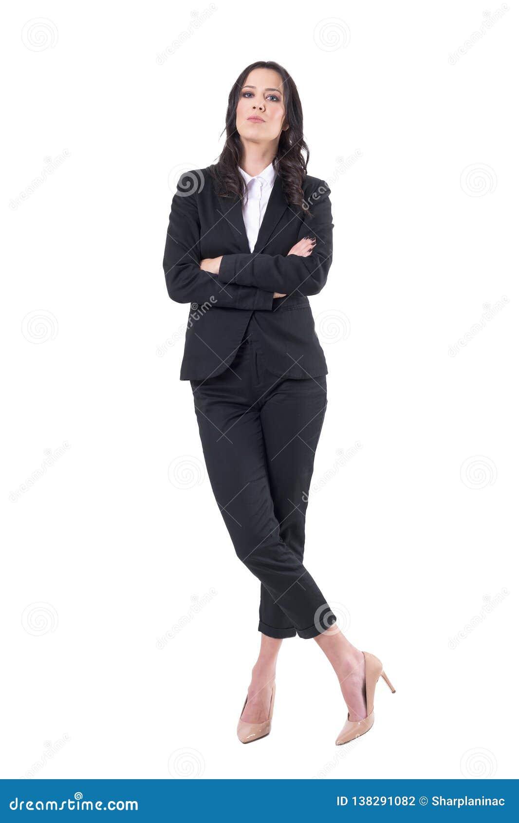 Ufna biznesowa kobieta w czarnym kostiumu z krzyżować rękami i krzyżującym nóg stać