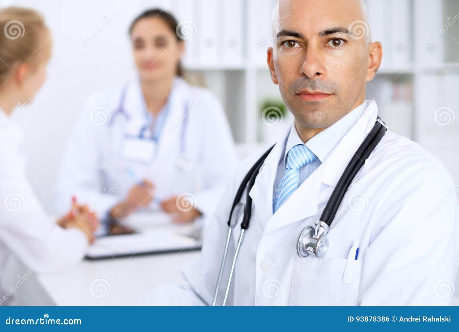 Ufny łysy doktorski mężczyzna z medycznym personelem przy szpitalem
