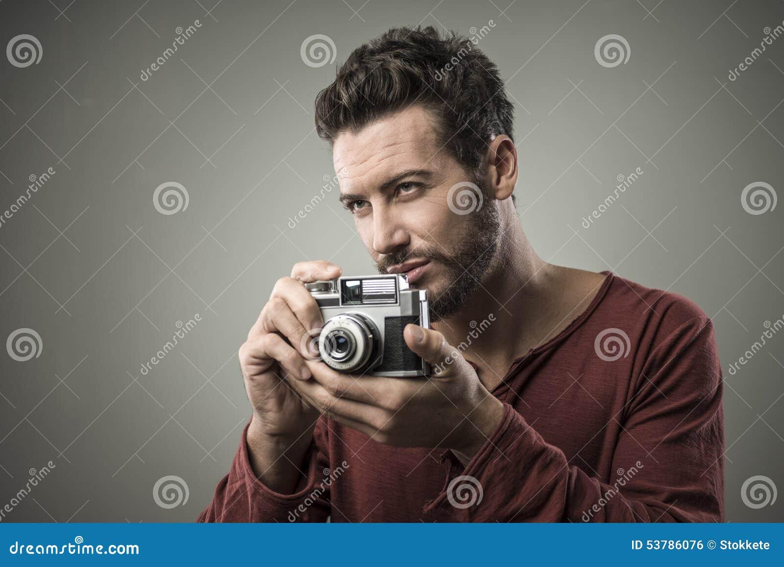 Ufny mężczyzna trzyma rocznik kamerę