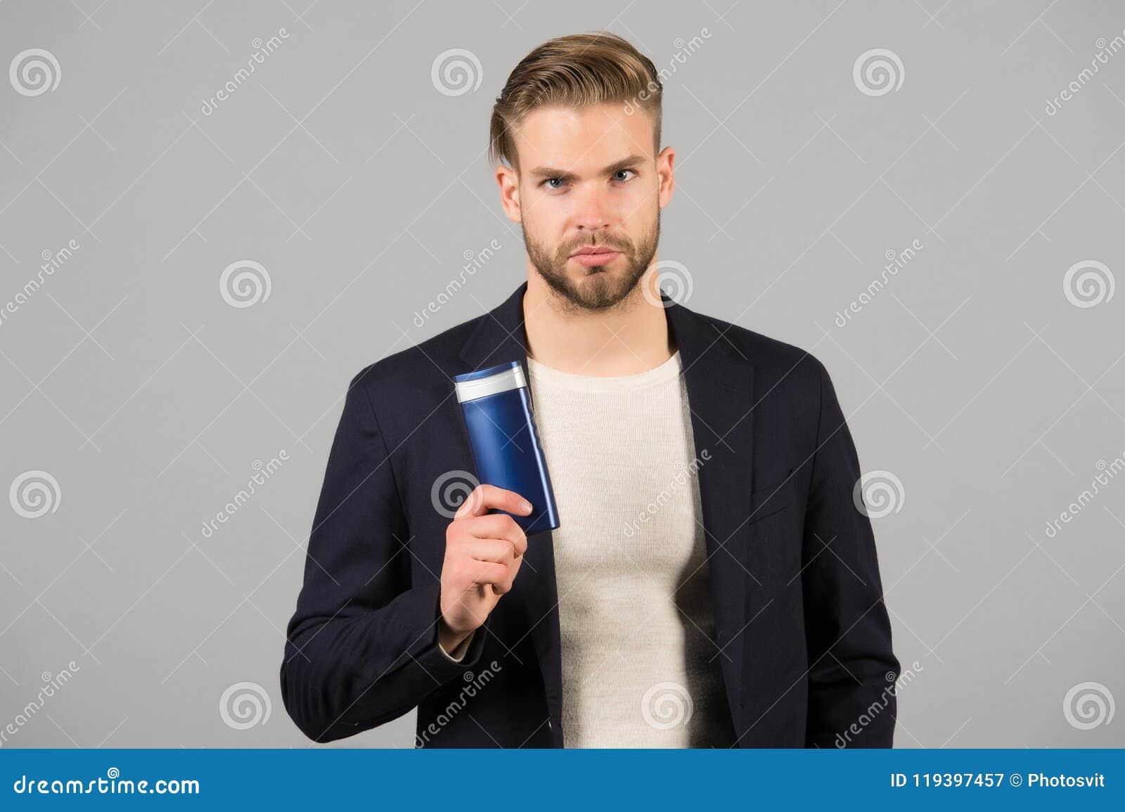 Ufny w włosianej opieki produkcie Mężczyzna fryzury chwytów butelki eleganckiego higienicznego produktu popielaty tło Przełącznik