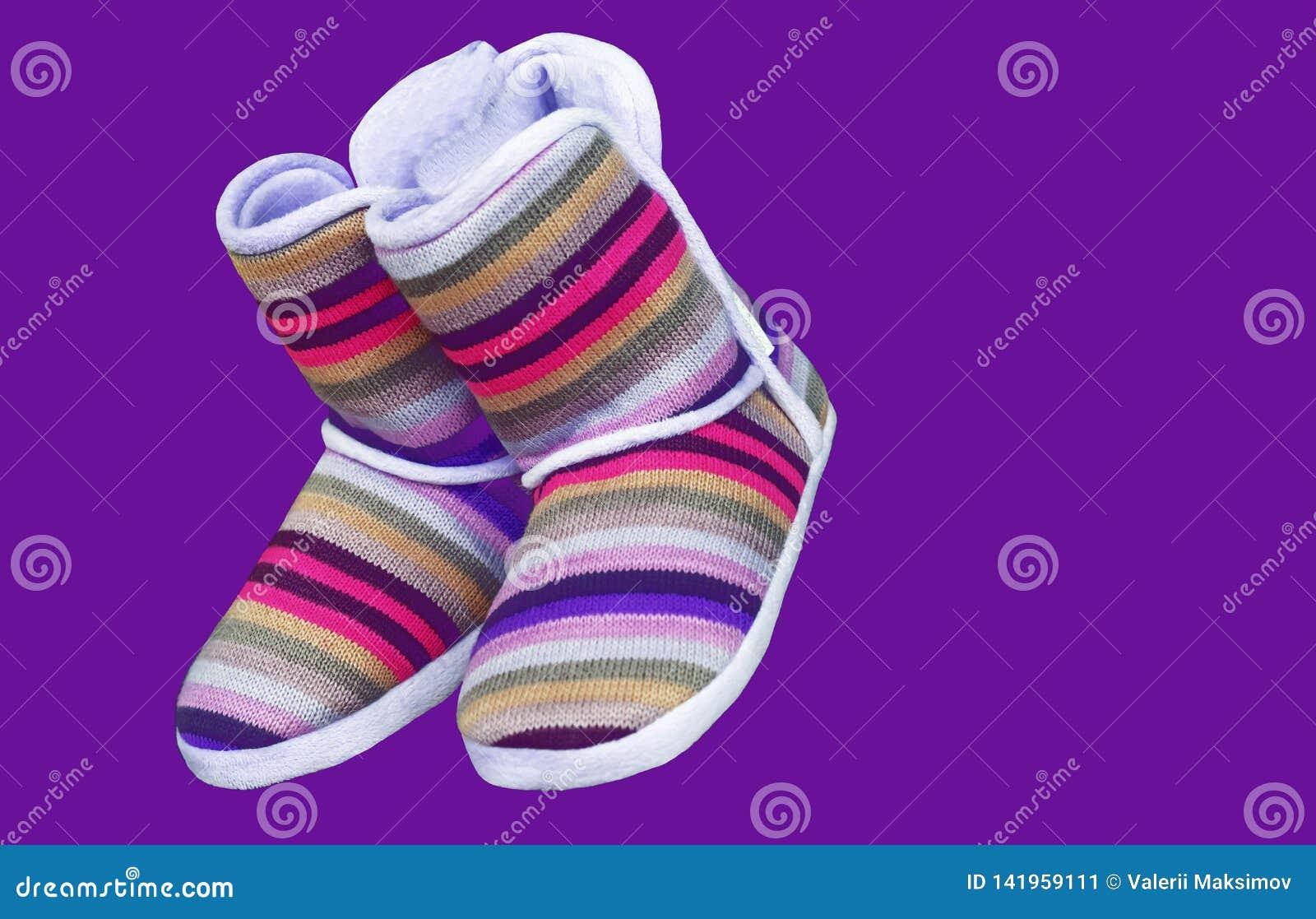 Uggs de lã com listras coloridas em um fundo roxo