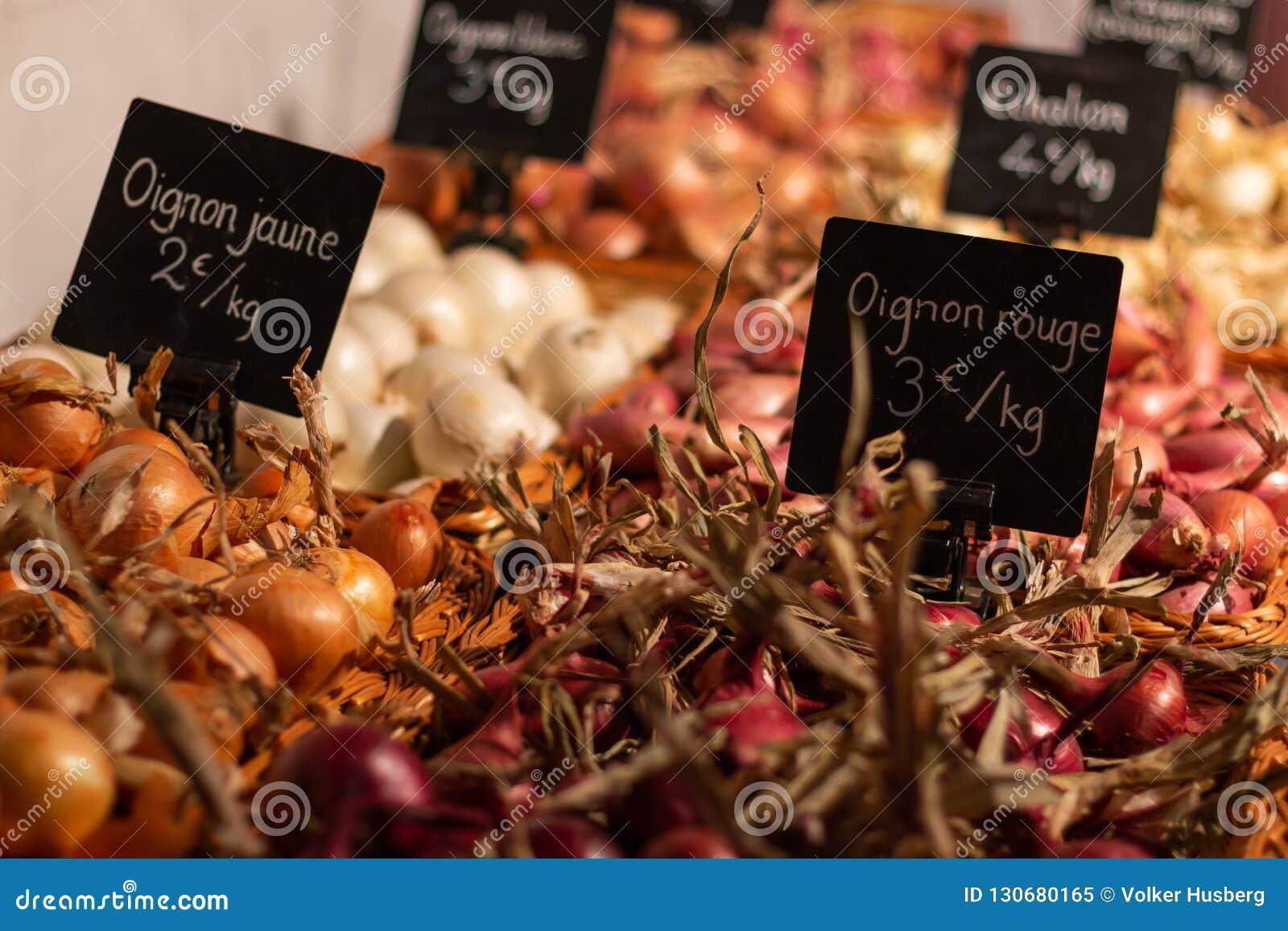 Uien van verschillende kleuren in een marktkraam met prijskaartjes