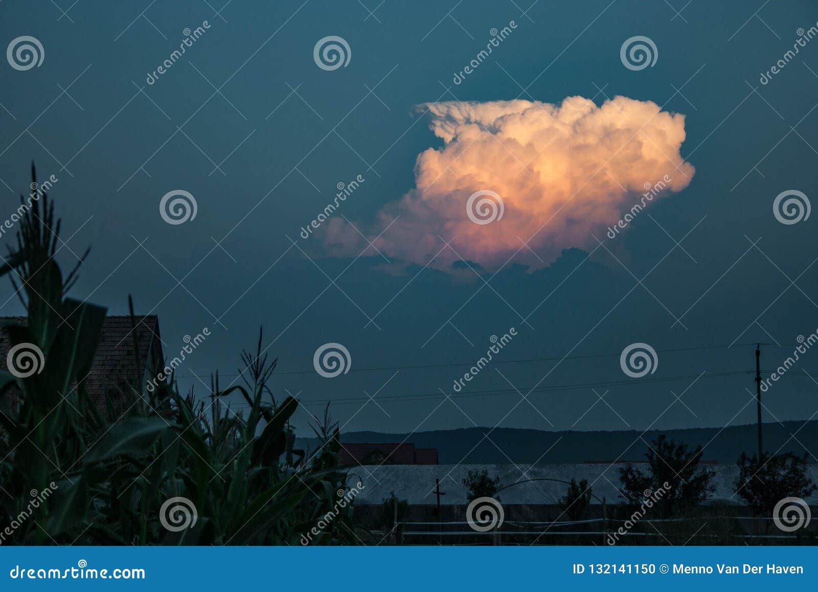 Uit de wazige laag stijgt een onweersbui en door de het plaatsen zon prachtig verlicht