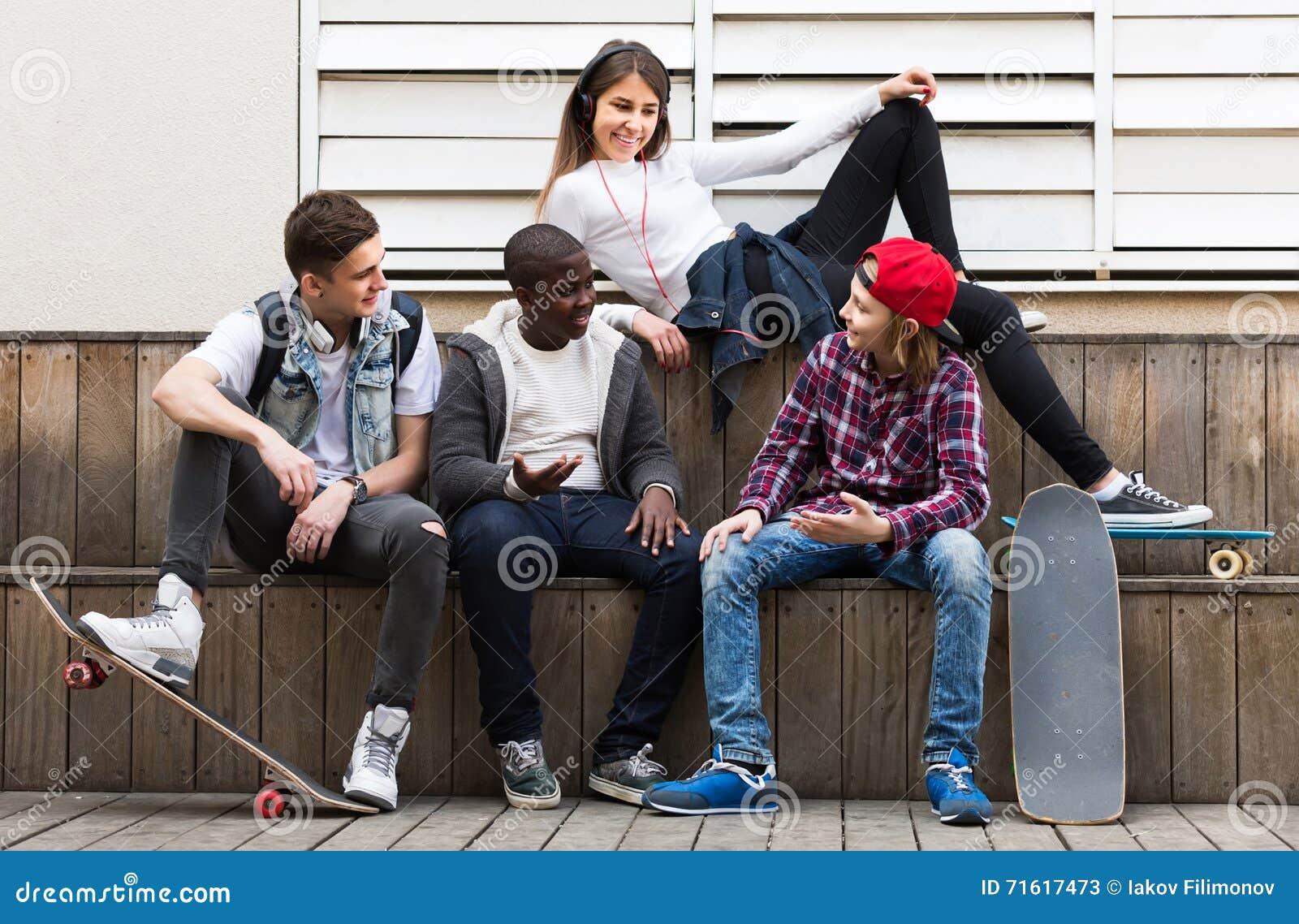 Uit in openlucht en meisje en drie jongens die somethin hangen bespreken stock afbeelding - Twee meisjes en een jongen ...