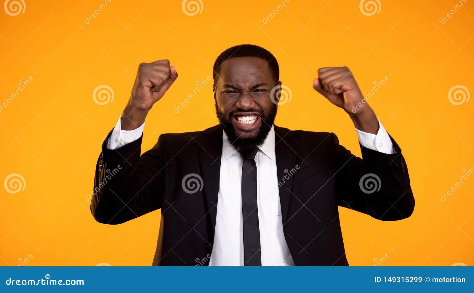 Uiterst gelukkige zwarte werknemer die en ja gebaar glimlachen maken, die bevordering krijgen