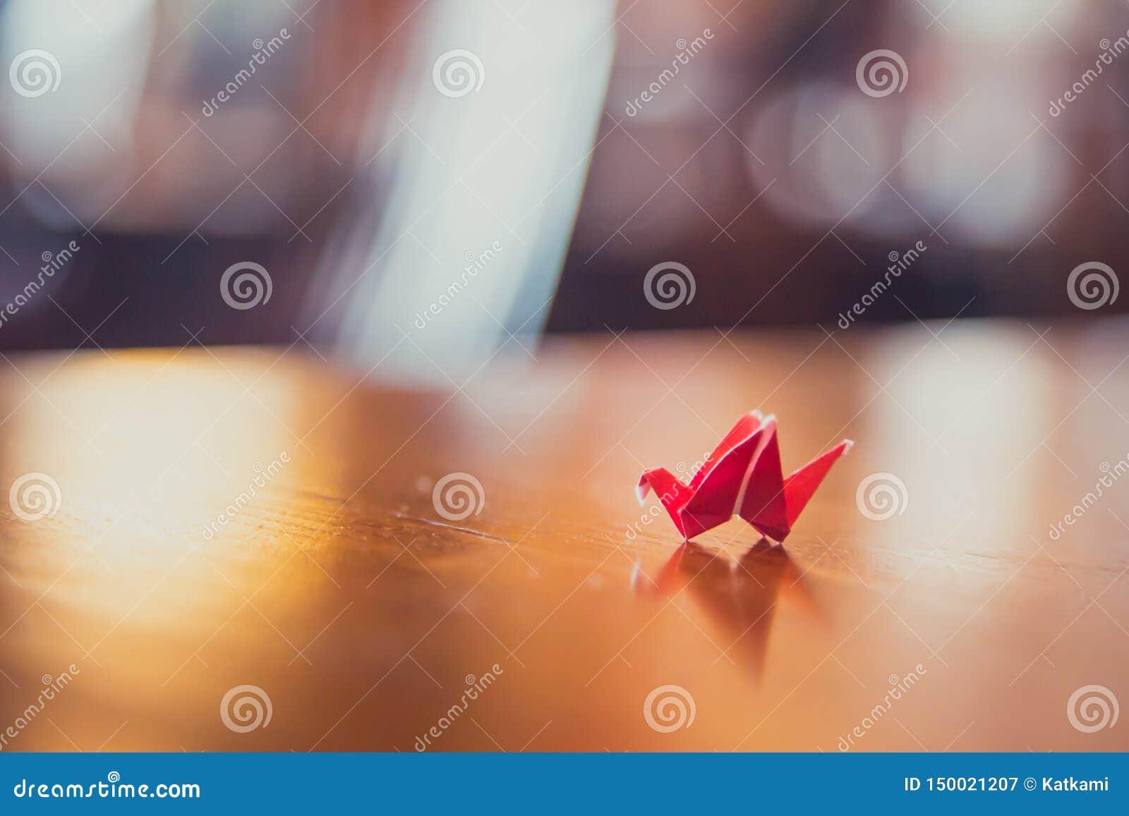 Uiterst kleine rode origamikraan op lijst