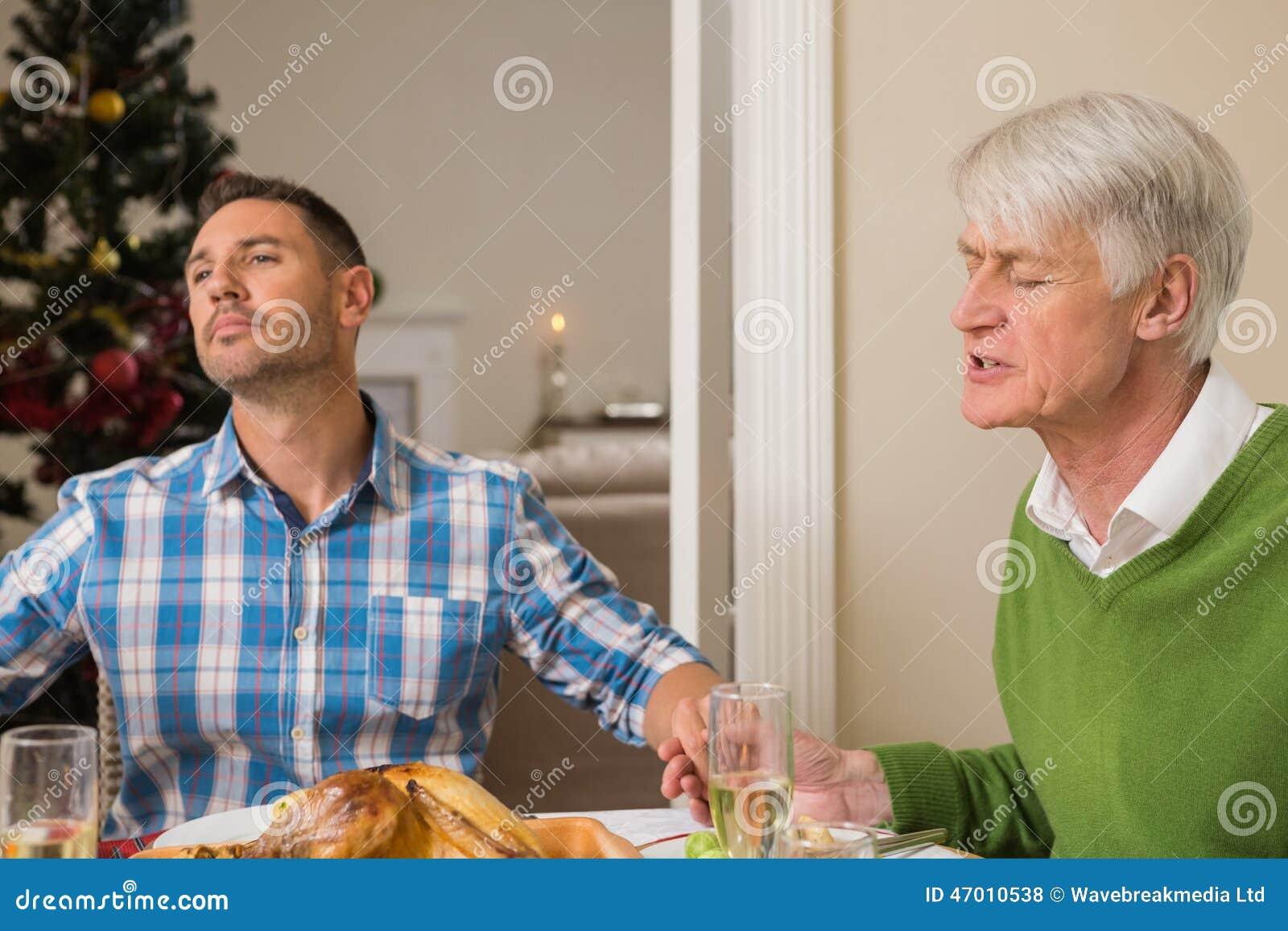 Uitgebreide familie die gunst zeggen vóór Kerstmisdiner