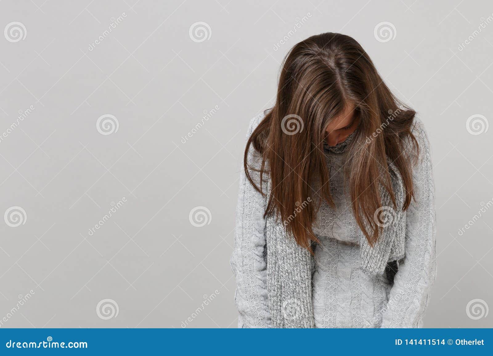 Uitgeputte jonge vrouw in grijze sweater, sjaal met verminderd die hoofd op grijze achtergrond, studioportret wordt geïsoleerd Ge