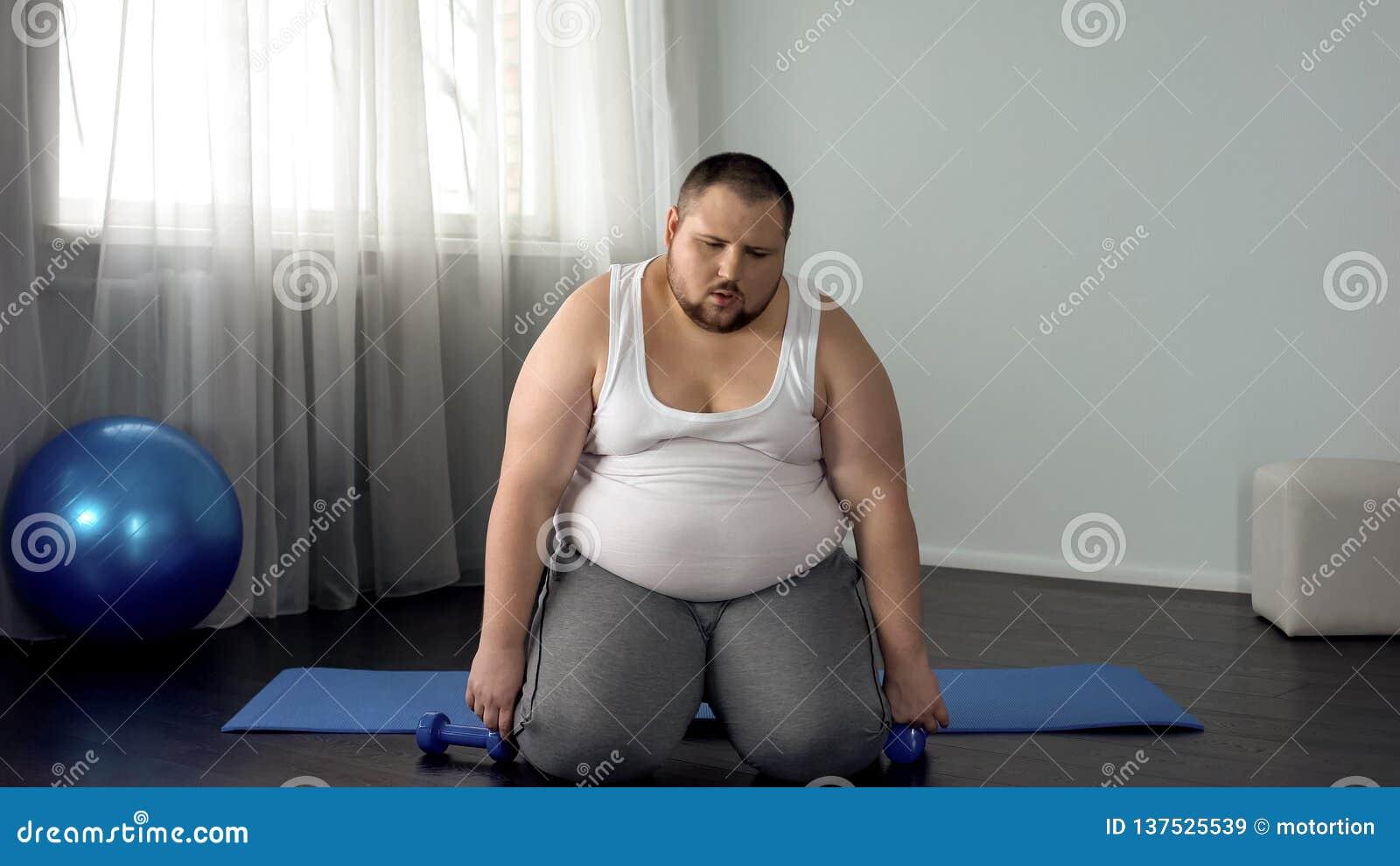 Uitgeputte vette mensenzitting op vloer met domoren, het vermoeien trainingprogramma, sport