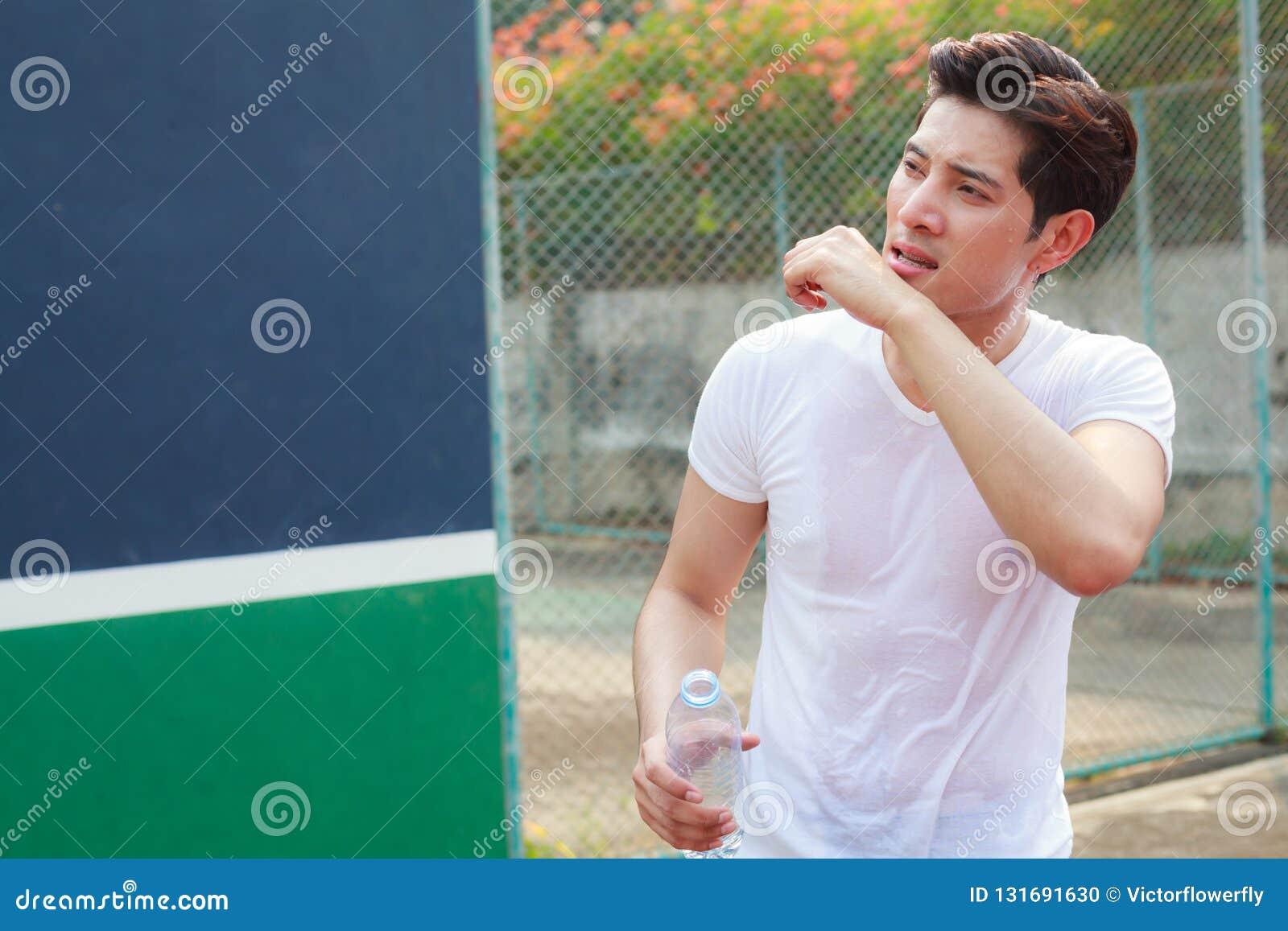 Uitgeputte zwetende atletische mens die schone fles de verse minerale hitte van de drinkwater openlucht onderzomer houden Gezondh