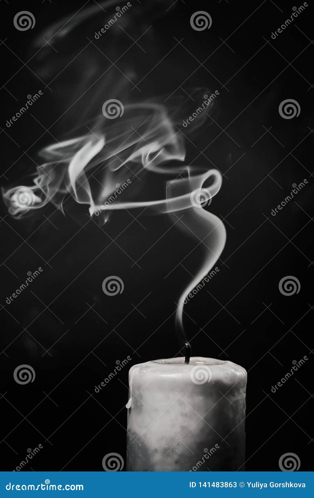 Uitgestorven witte kaars met rook op een zwarte achtergrond