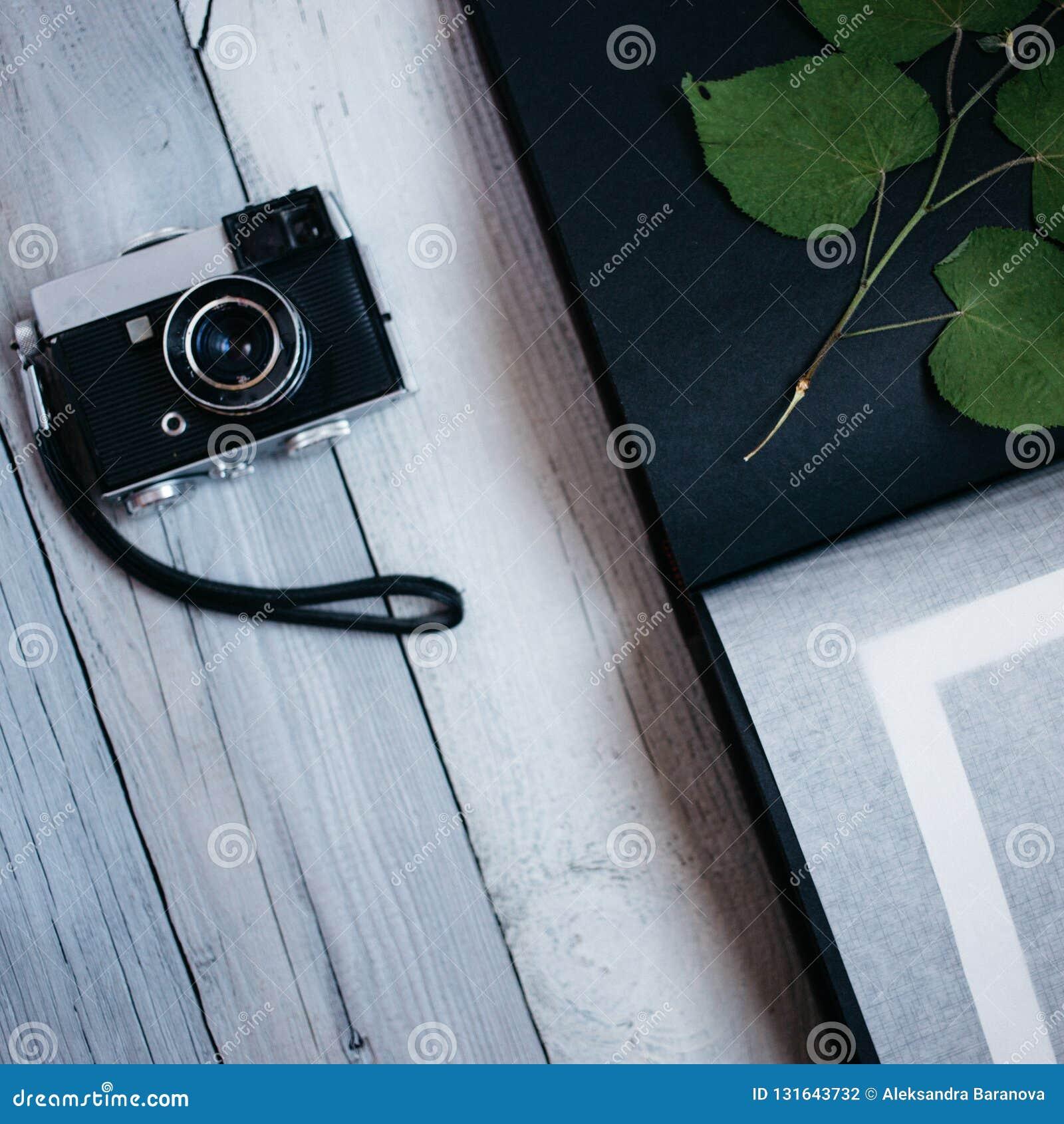 Uitstekende camera, een oud fotoalbum op de witte houten lijst