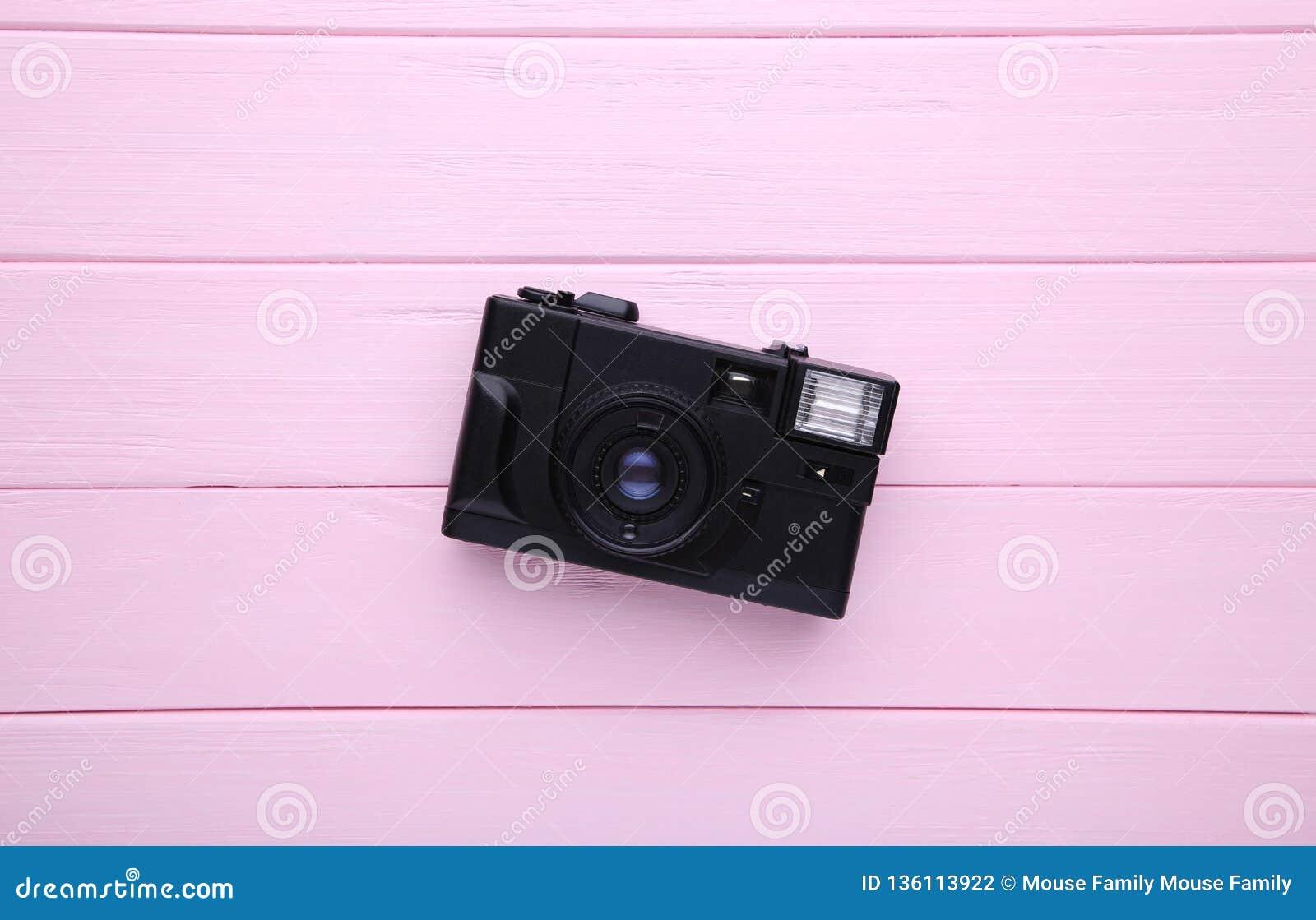 Uitstekende camera op roze houten achtergrond Oude fotocamera op achtergrond