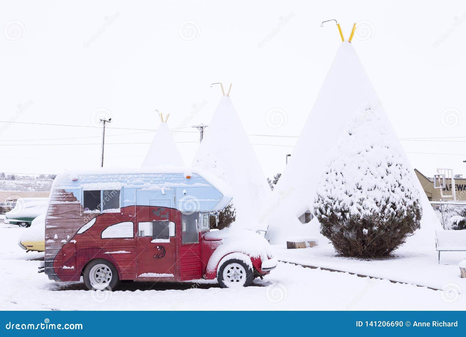 Uitstekende die het kamperen auto voor iconische concrete tipi van het de Wigwammotel van 1937 onder een laag van verse snowClass