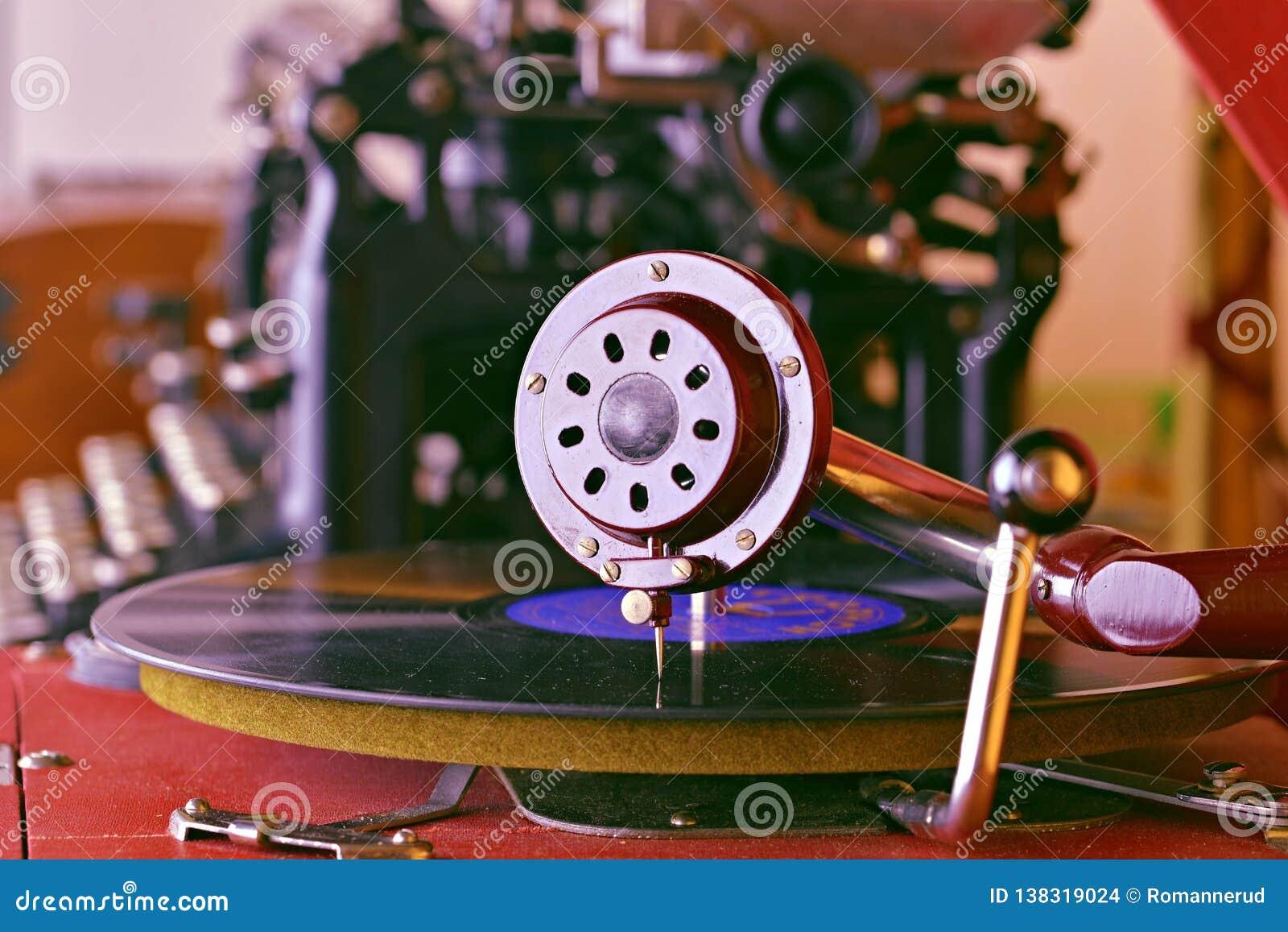 Uitstekende grammofoon met een vinylverslag op houten lijst Uitstekende schrijfmachine op achtergrond