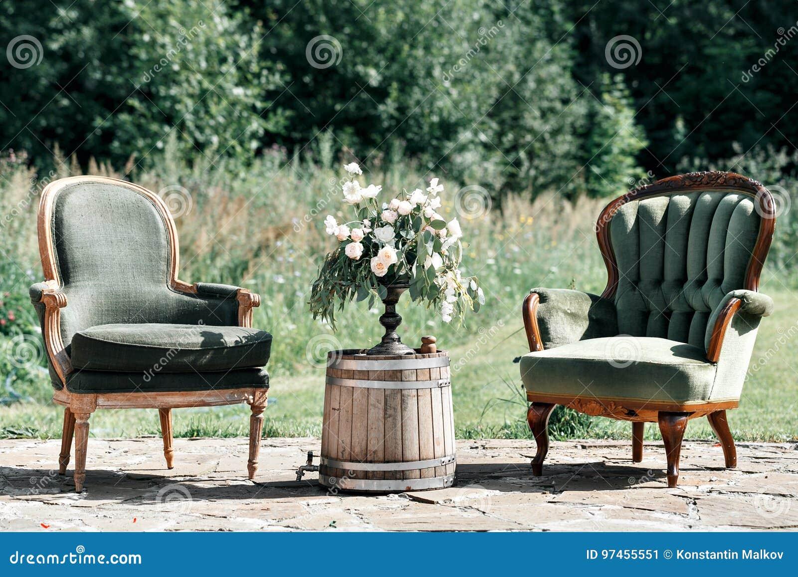 Houten Stoel Tuin : Uitstekende houten stoelen en lijst met bloemdecoratie in tuin