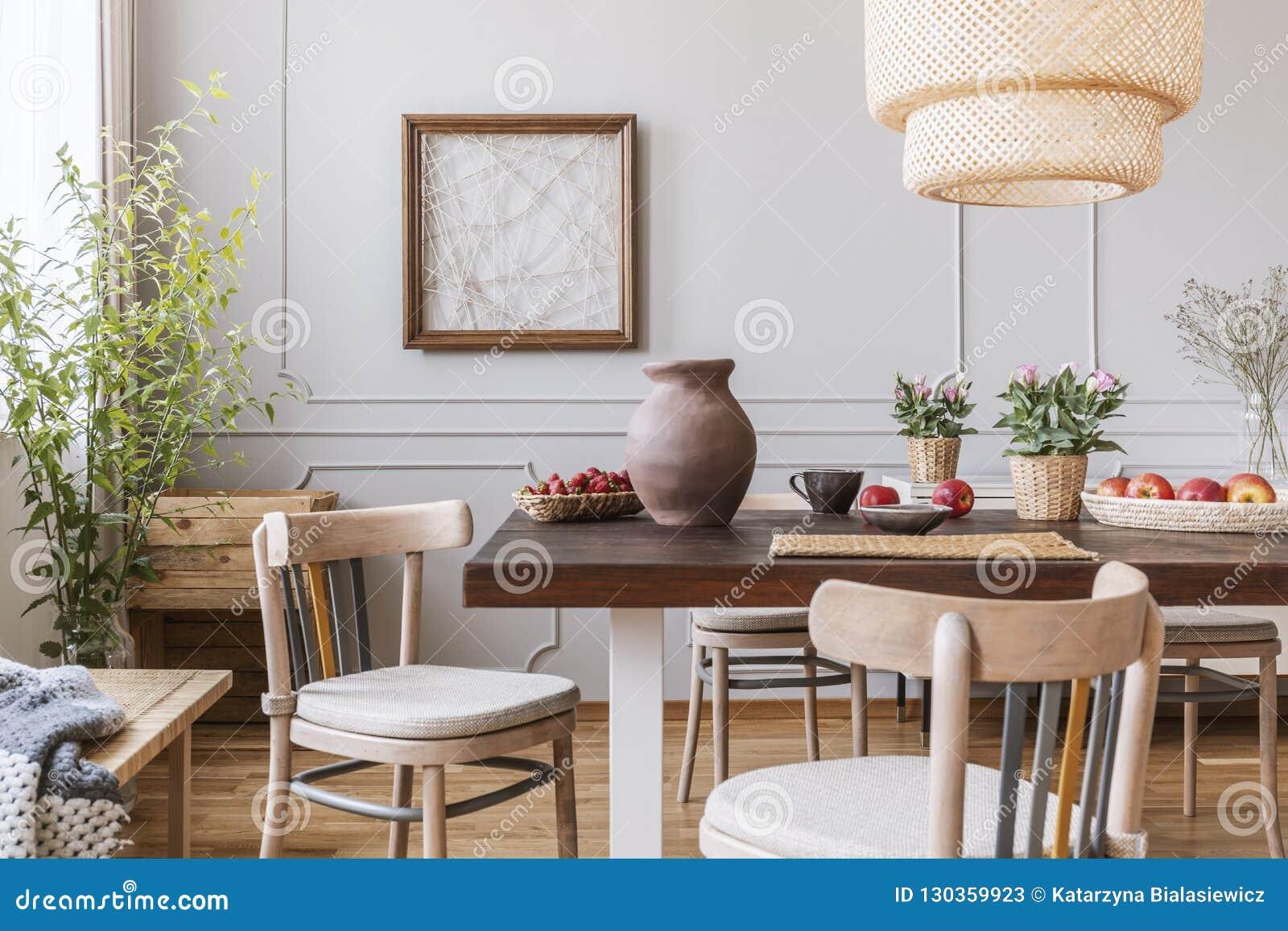 Uitstekende houten stoelen in woonkamer met lange lijst met aardbeien, appelen, vaas en bloemen op het, echte foto