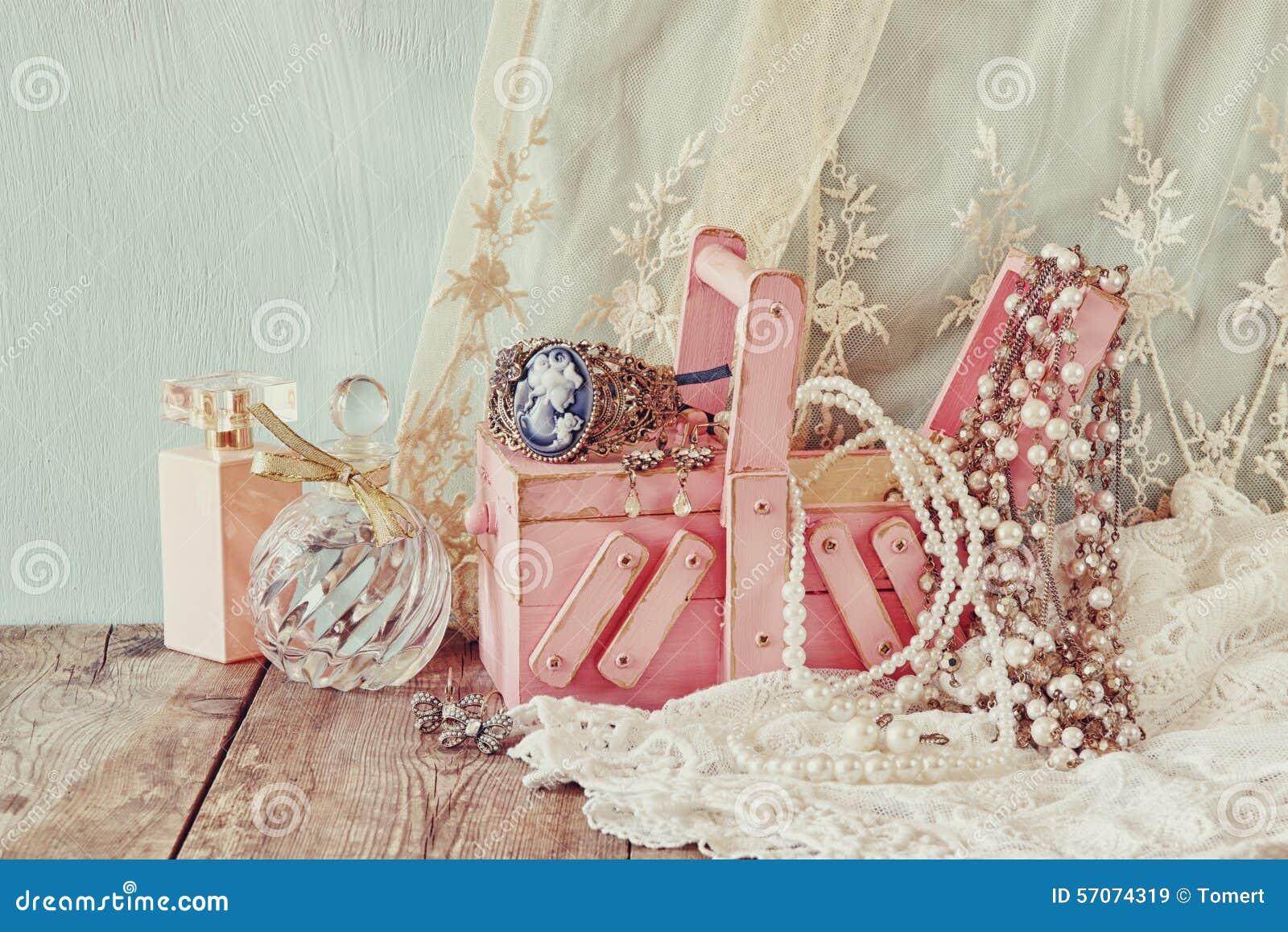 Uitstekende jewelelry, antieke houten juwelenvakje en parfumfles op houten lijst Gefiltreerd beeld