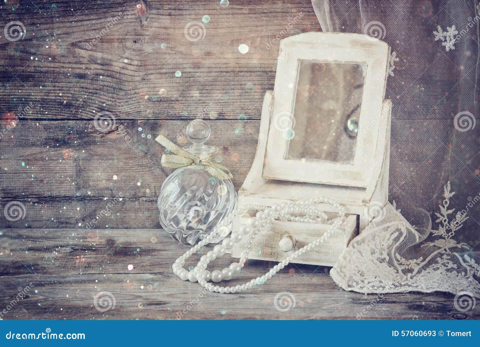 Uitstekende parels, antiek houten juwelenvakje met spiegel en parfumfles op houten lijst Gefiltreerd beeld