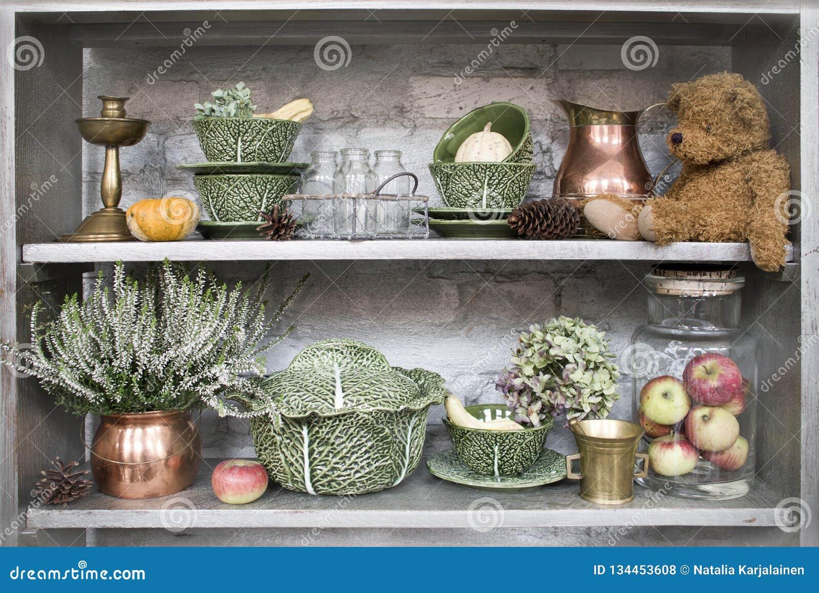 Uitstekende plank met antiquiteiten, schotels en speelgoed Heide, kandelaar, teddybeer