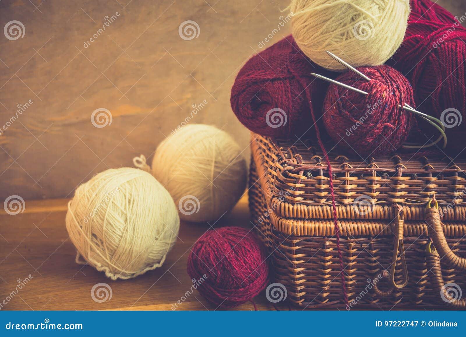 Uitstekende rieten clews van borstbollen van rood wit wolgaren, naalden op houten lijst, het breien, ambachten, hobbyconcept