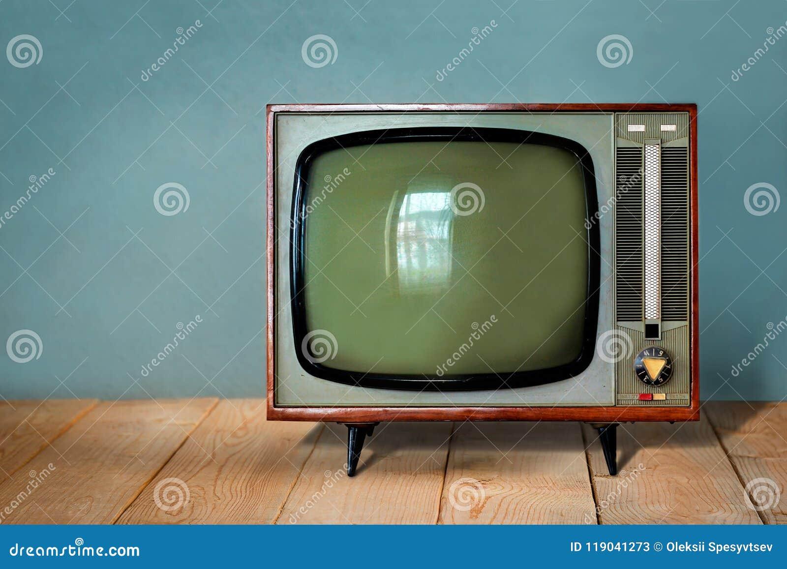 Uitstekende Televisie op houten lijst tegen oude blauwe muur