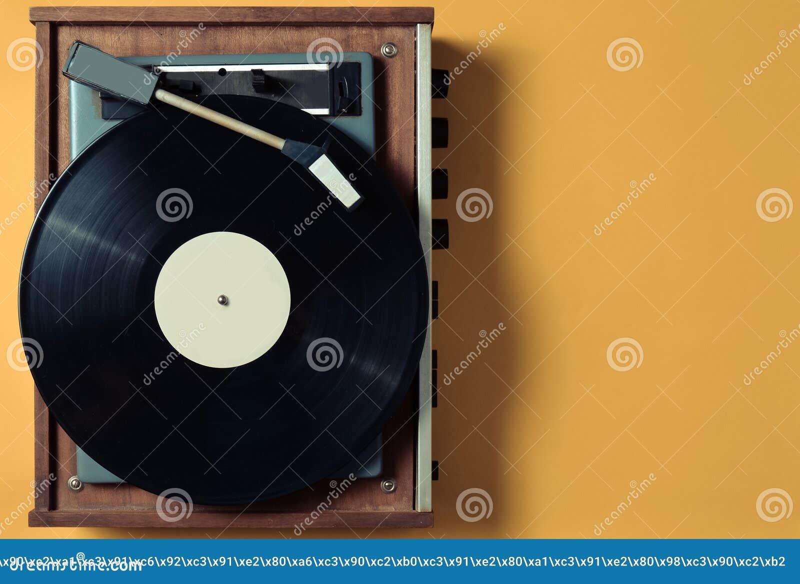 Uitstekende vinyldraaischijf met vinylplaat op een gele pastelkleurachtergrond Vermaakjaren  70 Luister aan muziek