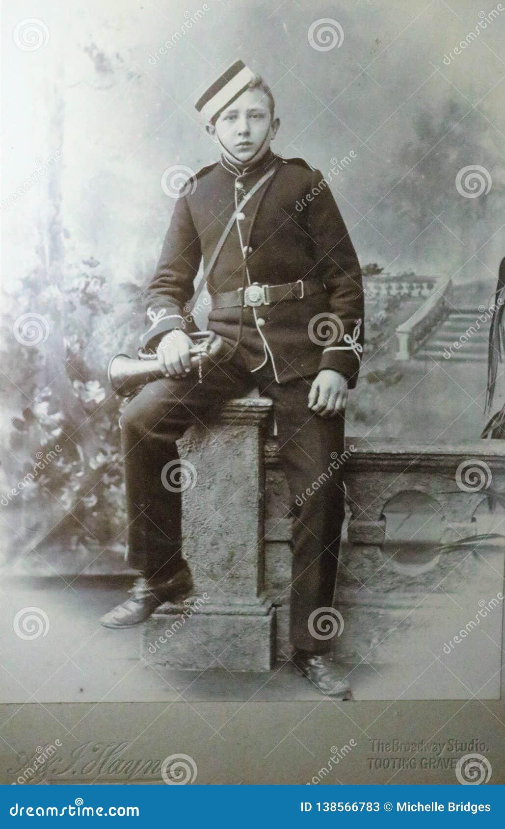 Uitstekende zwart-witte foto van een jonge jongen in militaire eenvormige holding een bugel