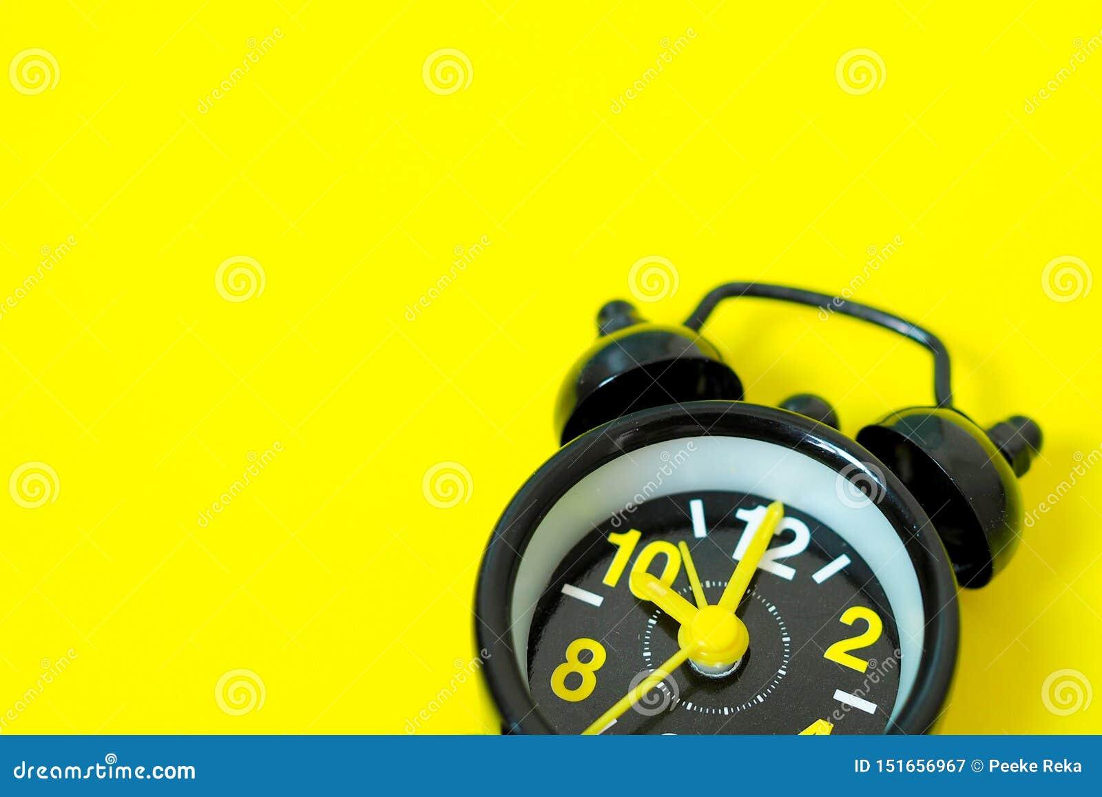 Uitstekende zwarte die wekker op gele achtergrond met ruimte voor ontwerp wordt geïsoleerd