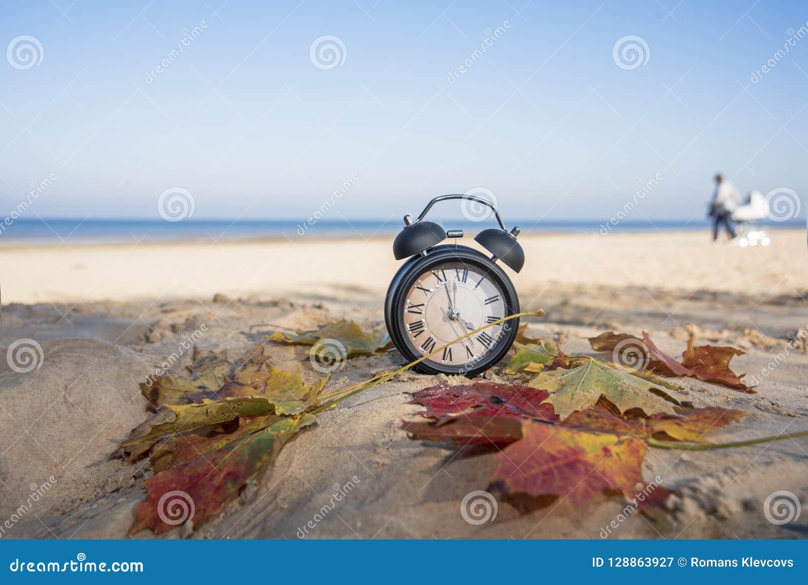 Uitstekende zwarte wekker op de herfstbladeren De abstracte foto van de tijdverandering