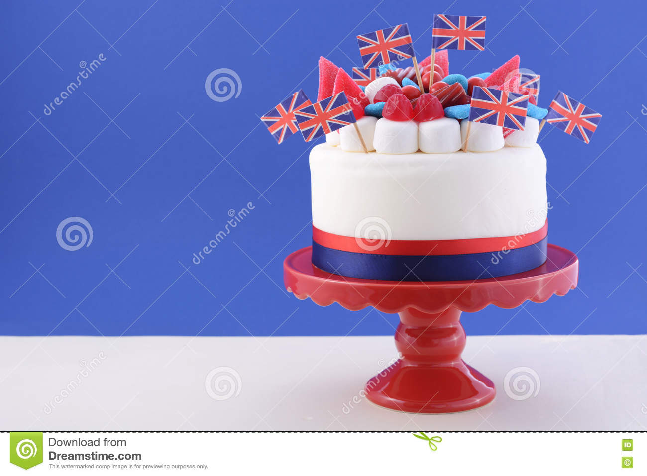 UK Celebration Cake With Flags Marshmallow And Candy Decorations On A Red Stand White Table Against Blue Background
