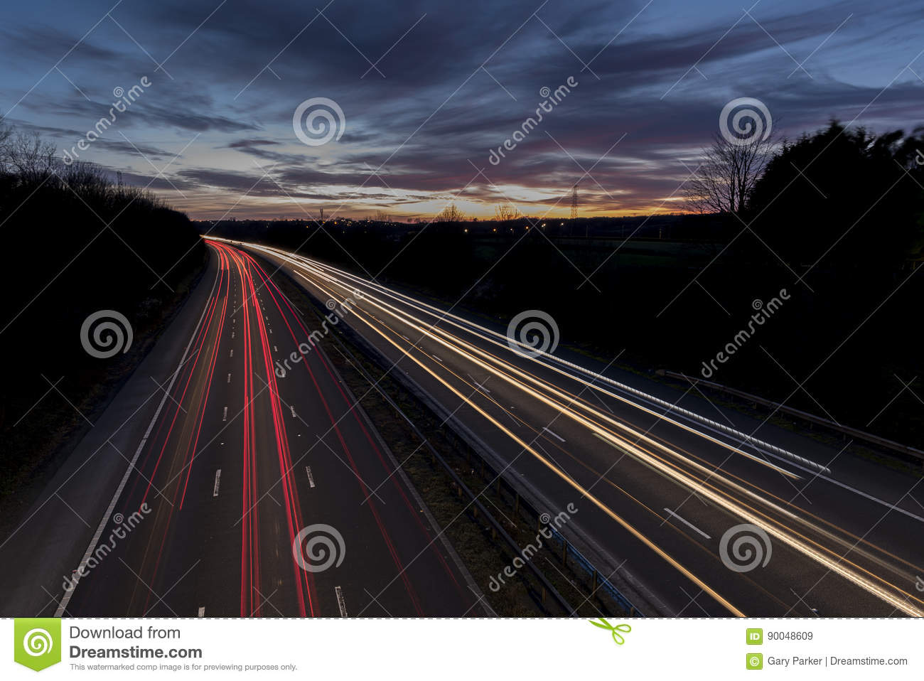 A UK motorway, at sunset, with light trails created by the traffic